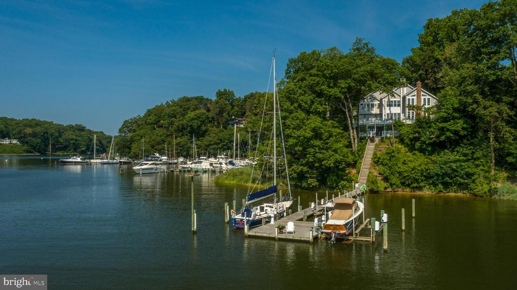 """Incredible opportunity to own a spectacular waterfront property in """"The Downs"""" overlooking the Severn River with a deep-water pier on protected Clements Creek with stunning water views from literally EVERY room!  This exquisite 1+ acre point of land with 427' of water frontage offers the perfect setting to enjoy panoramic views across Clements Creek and out to the Severn River.  This well-equipped, beautifully curated home invites tranquil living while effortlessly accommodating indoor-outdoor entertaining.  This home offers over 6,000+ sq ft of living space and over 1000+ sqft of exterior deck space on 3 finished levels with 5 bedrooms, 4 full baths (including an entry level bedroom with ensuite bath) and plenty of spacious rooms to accommodate everyone.  From the breathtaking 2-story great room with floor to ceiling windows, the cozy sun-filled den and stylish custom-built library and additional lower level Family room; to the newly remodeled gourmet Kitchen that is sure to delight and inspire the chef of the house; this move-in ready home is just waiting to host extravagant gatherings of family and friends or provide quiet moments to relax on the wrap-around waterside deck while enjoying the mariner activity and the endless views/sunsets.  As the evening winds down the Owner's suite with captivating Severn views, soaring ceilings, balconies and spa-like ultra-luxury bath provides a private, tranquil setting to refresh for the following day of enjoying the waterfront lifestyle!  The Downs on the Severn community has 2 marinas with canoe & kayak racks plus a picnic area, a clubhouse, community pool, playground and tennis courts.  Come explore the beauty of the Severn River.  Sailboater Alert!  The deep-water dock with 8ft water depth is equipped with 2 boat lifts (8,000lb and 20,000lb), shore power, sun deck and a massive 18'x50' boat slip, perfect for the boating enthusiast plus this Severn River setting provides quick access by boat to the Annapolis Harbor and th"""