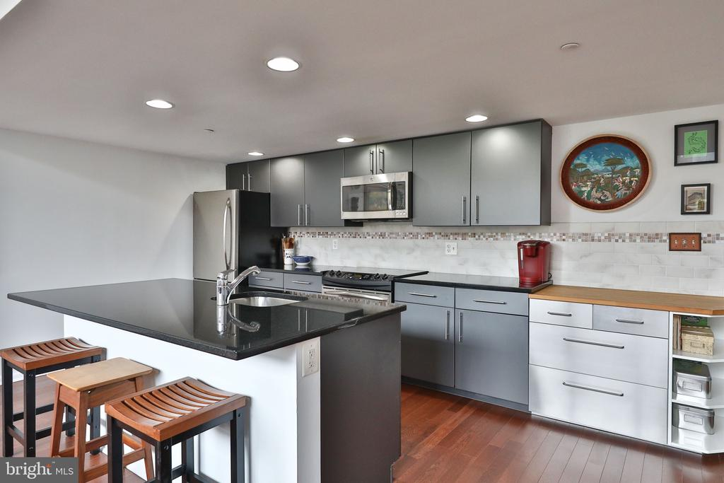 Stunning and spacious CORNER unit in the heart of Logan Square with a DEEDED, COVERED PARKING spot! This exceptional home boasts soaring, 15'+ ceilings, original architectural details, Northern and Eastern views, natural light in every room and, beautiful hardwood floors throughout. As you enter, you will notice an inviting hallway that features a half bath, utility/laundry room (with full-size, front load Bosch washer and dryer) with ample storage and, one of several oversized closets. The unit unfolds with an open-concept living area overlooking wall to wall, oversized windows. A true, cook's kitchen with oversized island, contemporary cabinets, stainless steel appliances, granite counters and ample seating space will be the hub for cooking and entertaining! The living room and dining room offer additional seating and entertaining options, as well as, space for a large dining room table. The main living area also offers two bedrooms (opening at top of the one bedroom wall could be enclosed), both with windows and huge closets, and a full marble bath. These two bedrooms would be perfect in the traditional sense, as well as, as an office, child's play area, art studio and/or guest space. You could also combine then into one! Take the custom, metal staircase to the master, loft bedroom (opening could be enclosed and door could be added), with en-suite, marble bath that boasts a spacious walk in shower. The expansive space easily allows for a California king-sized bed and a suite of bedroom furniture. Similar to the first floor, it is bathed in natural light and there is ample closet space. This unit also features a newer HVAC system (2020) and HWH (2019).  2200 Arch Street Condominiums is a full-service, New York-style loft building that offers amazing amenities and has one of the best locations in Center City. Just a short walk from Rittenhouse Square, 30th St Station, the Schuylkill River Trail, Comcast, (future) headquarters of Morgan Lewis Law Firm and the Parkwa
