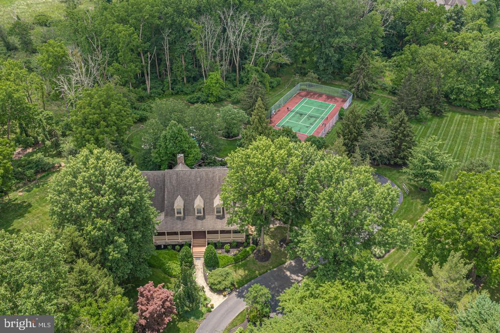 Come discover 5333 Ash Road, a timeless and tasteful countryside estate set on 10 impressively landscaped acres in the heart of Bucks County. Enjoy the privacy as you drive down the long winding lane to this picturesque setting. You will see this home was designed and built with thoughtful consideration to match the beauty of its surroundings. A bluestone path leads to the welcoming entry and wrap around porch with beautifully designed custom wood railing. Inside, the quality of craftsmanship shows through the home's attractive moldings, wainscoting and transoms which can be found throughout. Letting nature in, views of the meticulously maintained landscape can be seen from every area of the home. Gleaming hardwood floors grace the foyer which leads to all rooms on the main level. The spacious formal living room can be closed off for privacy with its stunning double wood panel colonial style doors and the lovely dining room seamlessly connects to the gourmet kitchen. For the chef in the house, this is so much more than a place to craft a meal, thanks to its custom, neutral tone cabinetry, porcelain farm sink, double wall ovens, and chic pendant lighting. In addition, there is a cleverly designed large center island, wood countertop, additional storage and seating. Windows wrap around the walls of the stepdown breakfast room which overlooks the spectacular patio and pool area and a pair of French doors lead outside lending the perfect spot for gatherings, both large and small. A large triple-paned window with transoms above highlight the cozy sunroom, which is currently being used as an office, featuring a bead-board ceiling and skylight along with clear views of the backyard. The sunken gathering room is the heart of this home with its stone floor to ceiling fireplace, cathedral beamed ceiling, wonderful built-ins and comfy window seats overlooking the lush landscaping. Conveniently located on this level is the generously sized Main Suite with access to the front po