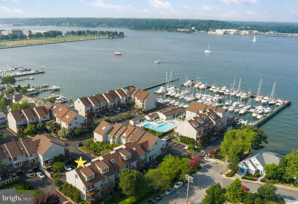 This luxury end-unit townhome is ideally tucked away in the quiet and serene marina community of Chesapeake Landing in the heart of Eastport. Accessible through a secured entry gate, pass the marina on the Severn River as you approach this three-bedroom, two-and-a-half bathroom completely remodeled townhome.  Every element of the home is impeccably remodeled and infused with the finest materials, fit, and finishes with rich hardwood floors, high ceilings, architectural moldings and design-inspired details. Refined principal rooms create a spectacular venue for entertaining, and transition seamlessly to cozy living spaces. The ultra-high-quality interior is functional, elegant and meticulously crafted, featuring an expansive dine-in gourmet kitchen with gleaming quartz countertops, stainless steel appliances, a large dine-in bar and private deck. The stunning family room is outfitted with custom built-ins, a wood-burning fireplace and sliding door that allows access to a private deck with lovely water views of the Severn River. The second level hosts two generously sized bedrooms, including the primary suite with custom walk-in closets, hidden custom laundry station, serene en-suite bath and private deck with views of the Severn River.  The third level presents the recently enclosed loft and newly built large dormer with ample windows that provide plenty of sunshine, extra headroom and a waterview, brimming with possibilities as a large bedroom, office or gym area . Continue to enjoy the home's amenities in the finished walk-out lower level where you can relax in the recreation area. Perfectly planned storage solutions are found throughout the home in the form of custom closets and built-ins.  A one car garage not only offers parking but features smart storage solutions.  The water-privileged marina community of Chesapeake Landing offers a private and secure location where you can revel in the tranquility of life on the Severn River including watching the Blue Angels