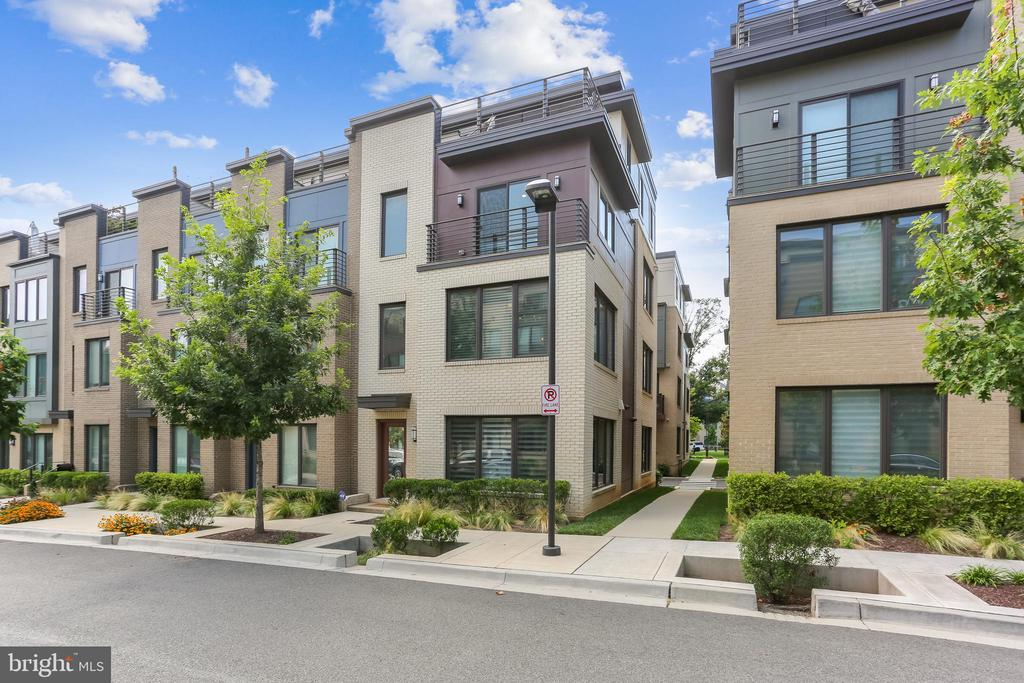 This Sophisticated Urban Townhome is city style living in a quiet Bethesda community.  The community has a 20-foot-wide pedestrian promenade the wraps around the townhouses and leads to a beautifully landscaped park area and a tot lot. At approximately 2650 sf AND four levels of living space, the Daniel Model, an END UNIT, rarely becomes available for sale.  EYA-built four years ago, it is unusually WIDE at 22 ft and has 4 bedrooms (with option for a 5th), 4-1/2 baths, A 2-car garage, a roof top deck and a balcony. It is the ultimate in luxury townhouse living with tall ceilings, an abundance of natural light, hardwood floors, designer lighting, stainless steel appliances including a gas 6-burner cooktop, quartz counters, kitchen island seating for at least four, a private balcony and a roof top deck. The entry level has a gracious foyer with an adjacent room that can be used as a bedroom, study or exercise room.  There is also a full bath, closet and a good sized 2-car garage on this level. On the main level there is an open concept plan that is anchored by a spectacular gourmet kitchen & built-in desk area at the center.  A large living area with a stunning fireplace wall & built ins and separate dining area are on either end of the kitchen.  There are windows everywhere providing natural light, a pantry, powder room and a balcony with room to enjoy a cup of coffee and a gas line for grilling. The upper level has a spacious primary bedroom with a walk-in closet AND an additional two-door closet, a primary bath with a double vanity, linen cabinet, and a glass enclosed luxury shower.  There are two more bedrooms on this level plus another full center hall bath and a laundry area. On the loft level, the Sellers chose to open the up the space for a large open entertainment area for seating & exercise equipment.  There is a full bath and closet so a fifth bedroom could be carved out in this space.  In addition, the roof top deck with retractable awning and gas fireplac