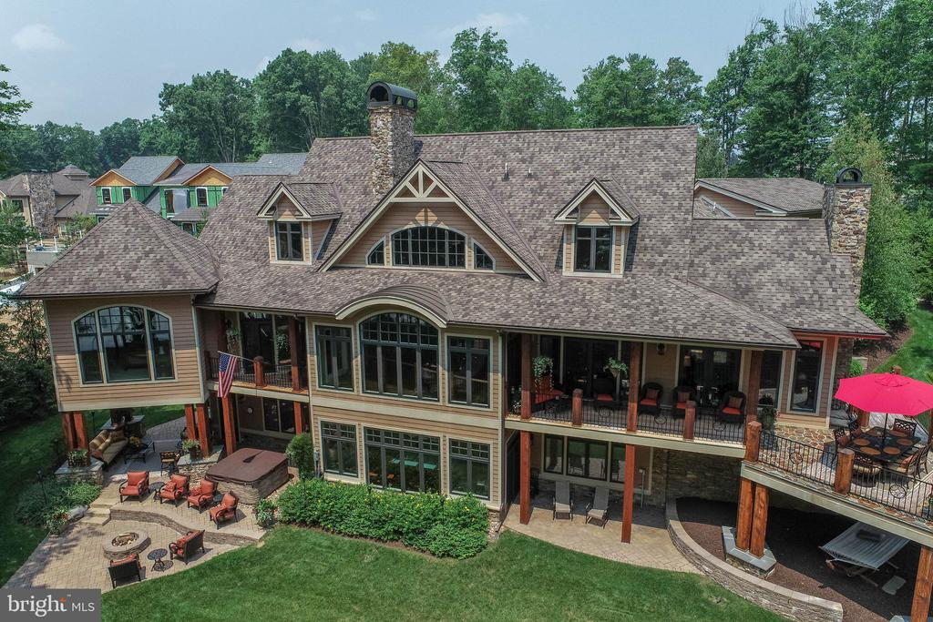 One of the lake's finest lakefront properties in one of the lake's best communities.  This 5 + suite floor plan, offers the highest level of quality and craftsmanship, evident from the moment you enter the driveway.   The main level features a professional level kitchen, a grand great room with high ceilings and a beautiful stone fireplace.  The eating area overlooks the covered porch and lake area.  A separate den with stone fireplace is the perfect place to escape.  The main suite includes a private den, fireplace, whirlpool tub, tile shower and walk-in closet.  The lower level includes two lakefront suites, a large game/family room, a beautiful bar area, wine cellar and enough additional storage for all your toys and extra possessions.  Above the 3 car garage is a grand theatre room/bonus dorm area.  The exterior is even more extraordinary, with 2 covered porch areas, deck, firepit and hot tub.  When it is time to hit the lake, the level lakefront area includes a large dock with sitting area and allows for 3 power boats.  The grounds are meticulous and the location is as good as it gets.  It won't be available for long.  Make plans to see it today.
