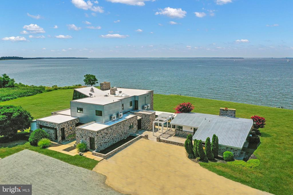 Wake Up with Breathtaking Sunrises and Close Your Day with Colorful Sunsets in Your One of a Kind Chesapeake Bay Custom Contemporary Waterfront Home on a Very Private 4.67 Acre Lot !   Newly Renovated with an Eye for Entertaining, You and Your Guests will Enjoy the the Dramatic Lines, Walls of Windows, Panoramic Views and Open Spaces That will Easily Accomodate Large and Small Gatherings.   This 8140 SF,  6 Bedroom, 5 Full Bathrooms and 2 Half Bathroom will Easily Sleep 16 People.  The Main House has a main level Primary  Bedroom with Ensuite Bath and Private Patio, Upper Level Primary Bedroom with Sitting Room and Ensuite Lavish Bath, A Guest Room with Ensuite 1/2 Bath and then a Bunk Room with 4 Built In Bunks!  The Attached Guest House has a Second Kitchen, Living Room, Guest Bedroom and Then Bunk Room with 4 Bunks Again.  This Home Can Be Accessed with Private Entrance or Via Spacious Foyer.  Nestled on 4.67 Private Acres with 900' on the Chesapeake Bay, this Estate Is  Perfect   For Family /Extended Family  or Weekend Retreat with Entertaining and Guests.   Yes....You Do Deserve This.  Schedule Your Tour Today and Experience the Chesapeake Bay .