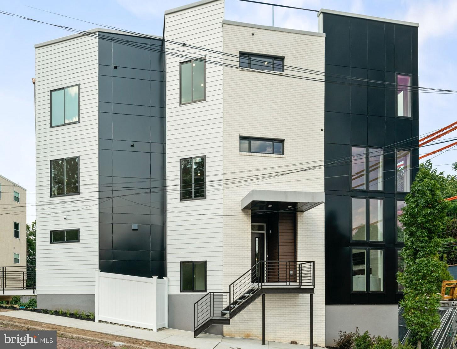 Welcome to 4803 Silverwood - boasting over 4,200 square feet, 3 car parking, a two-story family room, and one of the largest roof decks you will find in Manayunk! This single-family new construction home features 4 spacious bedrooms, 3.5 bathrooms, a second living room on the 3rd floor, patio off the living level, and comes with 10-year tax abatement and 1-year builder warranty. The first floor features a flex space that can be used as an office, workout room, or storage room. Complete with closet storage and mechanicalroom. Garage entry to first floor - garage fits two-car tandemparking and 1 car parking in the driveway. Additional area in garage for more storage. As you enter the front door, a large coat closet fits your guest's need who will be wowed by your spacious open-concept kitchen, dining, and two-story family room which will not disappointyou! The chef's kitchen features high-end appliances, hood over Viking 6 burning range with pot filler, custom kitchen cabinets, double thick quartz countertop on the island with large stainless steel oversized sink, and wall oven and microwave. The double door pantry is spacious for all of your kitchen storage needs. You will pass the large half bathroom on your way out to your outdoor patio, perfect for grilling and enjoying the outdoors. The two-story family room is truly thehighlight of this home. With floor-to-ceiling shiplap fireplace, stunning windows, and a custom built-in wet bar - perfect for entertaining. Upstairs you will find a second living area that overlooks the living room, two spacious bedrooms with double door closets, alarge full bathroom with double vanity sinks, and complete withthe laundry room. Continue up to the owners living level and 3rd guest bedroom and full bathroom and walk-in shower. The owner suite will blow you away with how large it is and oversize walk in closet with custom organizers. The on-suite bathroom features HEATED FLOORS, a gorgeousblack tub, double vanity, and walk in shower 