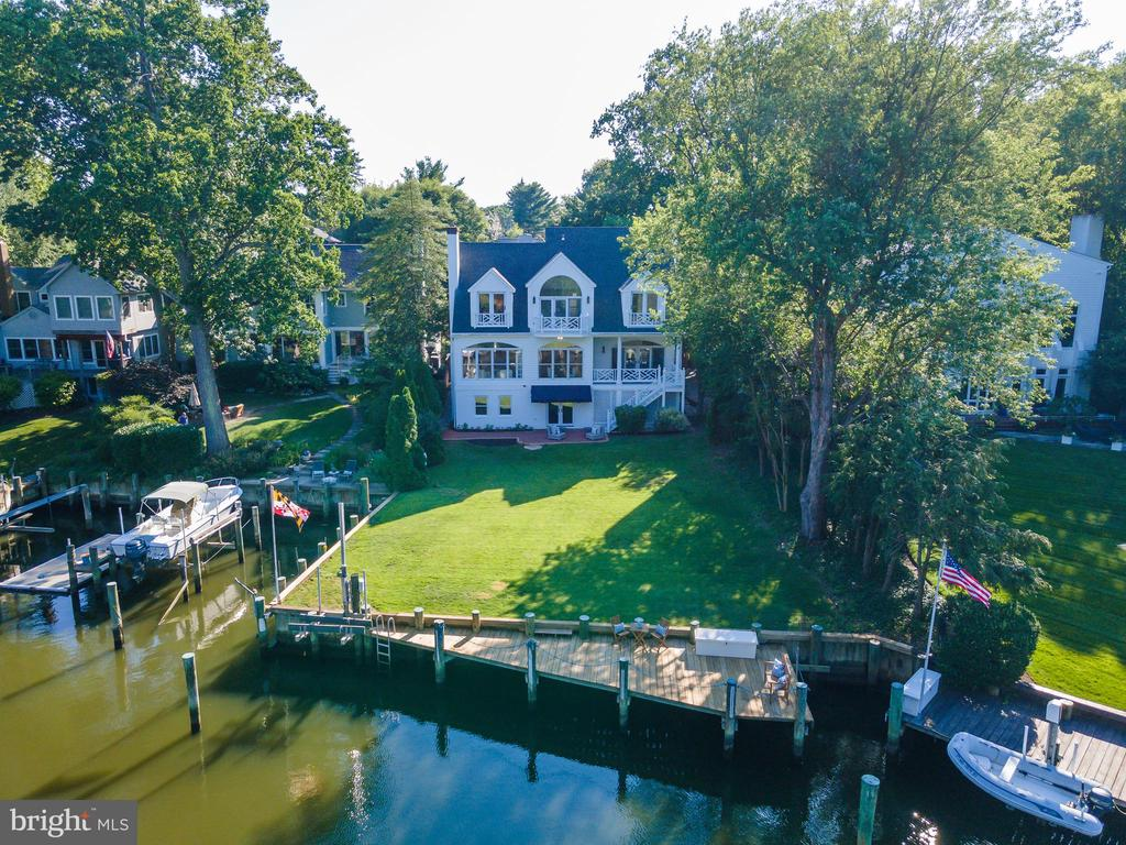 Eastport waterfront!  Celebrate the Annapolitan lifestyle and enjoy unparalleled deep water all year long.   Waterfront properties like this rarely come to market.  This captivating home with fabulous views of Wells Cove and Spa Creek is available for the first time since the property was developed.  Perfectly sited on a spacious 1/3 acre flat lot with 115 ft of waterfrontage on Wells Cove, the two slips with 7ft water depth and boat lift provide the ideal setup for the boating enthusiast.  This highly sought-after Eastport location is conveniently walkable to everything Eastport and Annapolis has to offer.  Tucked away on a private cul-de-sac, this stately custom home with detached 2 car garage was custom built to the highest standards and lovingly cared for and thoroughly enjoyed for over 30 years by the original owners. Beautifully curated finishes artfully blend the formality of an East Coast manor with casual comfort and an optimal floorplan for entertaining, offering a true waterfront escape.  Featuring beautiful cherry hardwood floors, extensive millwork, 2 fireplaces, 10' ceilings and 8' doors on main level, elevator, beamed ceiling in Family Room and large windows that capture the water views from almost every room, additionally the waterside veranda off the kitchen is great for dining al fresco on cool summer nights. With 4 bedrooms and 3.5 baths there is ample space for family and friends to spread out.  The owner's suite on the upper level encompasses a large portion of the waterside of the home and captures panoramic views of the water and surrounding neighborhood and boasts a spa-like bath with double sink, separate tub and shower and large walk-in closet.  This home has been designed to provide multiple opportunities for additional square footage including 400 sqft of unfinished space above the detached garage, perfect for a guest room, office or gym.  The fourth floor offers 800 sqft of already insulated and floored attic space and the light filled l