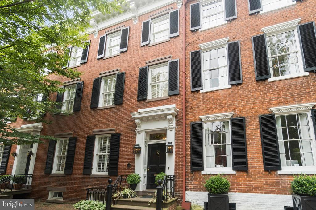 Located in Georgetown's prestigious East Village, this grand Federal home offers gracious open living on five finished levels. Originally built in 1810, the all-brick residence has been impeccably maintained and updated while featuring exceptional period details in every room. Substantial crown moldings, hardwood floors and nine fireplaces with impressive surrounds are but a few of the home's refinements. Through the gracious foyer, the main level boasts formal living and dining rooms, each featuring built-ins, a fireplace and soaring ceilings. The table-space gourmet kitchen provides marble countertops, an oversized island with extra seating, Thermador 6 burner gas range and integrated fridge, freezer, wine cooler and dual dishwashers. Just off the kitchen the family room provides access to the private rear patio, ideal for indoor-outdoor entertaining. Upstairs, the primary suite encompasses an extraordinary dressing room with island storage, ample shelving and two en-suite bathrooms. The generously proportioned bedrooms all offer abundant natural sunlight, fireplaces and spa-like bathrooms. The lower level recreation room offers significant activity space, substantial storage and immediate exterior access. The property also features an elevator, which is accessible from all levels. Outside, the professionally maintained garden and terraced patio provide mature shade trees, a serene fountain and ample entertaining space. Off street garage parking for two cars conveys. Ideally located on a prominent Georgetown street, 3026 P Street NW was also the former residence of the 56th Secretary of State, Henry Kissinger.