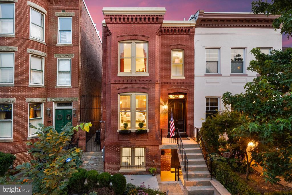 """Only on rare occasions does a home come along that is so astonishing in its uniqueness, so unparalleled in its size and condition, and so abundant in amenities. 613 Constitution Ave NE is just such a home. Built in 1887, this stunning, semi-detached, grand estate row home, with over 4600sf** across 3 impeccable levels, delivers more than you ever hoped to find on Capitol Hill. Smart, sophisticated, and truly special.  The expansive size is enough to turn heads, but when combined with an uber-convenient location, exceptional condition, """"green"""" energy features, grand entertaining spaces, an in-law suite, and a huge attached 2-car garage, this grande dame instantly becomes the hot topic of conversation and will be among the most sought-after homes on the Hill.  The impressive street presence draws you in w/ the elegant design of the facade's brickwork (professionally re-pointed within the past decade) & period details that remain beautifully intact inside and out. You will immediately be wowed by the huge open-plan formal living & dining spaces, and the bright sunlight streaming in from 3 exposures. It is a perfect space for large-scale entertaining, with easy flow to the private patio for indoor/outdoor entertaining. A wood burning fireplace, charming box bay, exceptionally tall ceilings, and gleaming hard pine floors add to the allure.  Next the beautifully appointed kitchen (renovated in 2019), with ample cabinetry, a large island, quartz counters, top grade stainless steel appliances, and a stunning view of the patio with its flowering trees & plants. This is where a typical Hill home might end, but not here. The kitchen leads to a breakfast room with double glass sliding doors to the private patio, and then beyond to an enormous family room w/ built-in cabinetry and bar, another wood burning fireplace, and a skylight. The large, private brick and slate patio is also accessed from this area and features a built-in grill and raised planting beds. To complete this le"""