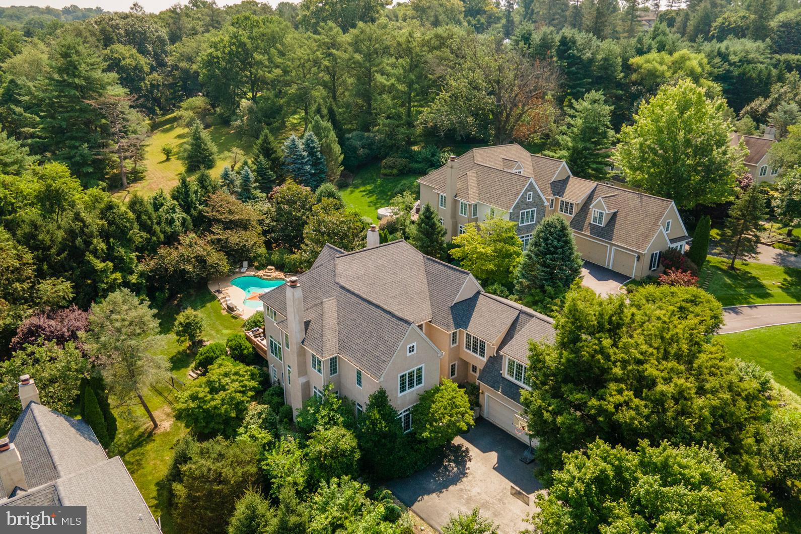 This beautiful transitional Colonial home sits notably on a quiet cul-de-sac with a private backyard amidst an active and coveted neighborhood of 30 homes.  Your own oasis: the entry awaits with loads of natural light and a two-story foyer that opens into a formal living room complete with fireplace and transitional millwork.  A spacious corner office is in the front.  Stunning hardwood floors lead your way from the living room to a large and light-soaked dining room adorned with two massive picture windows.  The chef's kitchen features a large island with seating and commercial stainless steel gas Viking cooktop, double ovens and refrigerator.  There is little end to the storage this kitchen provides and also includes a command center/office, walk-in pantry and a considerable breakfast room with a wall to wall window and captivating natural views - it's all about the light in this home.  A family room open to the kitchen boasts tremendous windows and vaulted ceiling height offering a front row seat to yet another spectacular view, home to the second fireplace and access to the deck and outdoor entertaining space including an inviting pool with a waterfall and spa. Upstairs has a great primary suite with a sitting room, massive walk-in closet and dressing area, spacious marble bath with a large jetted soaking tub and double shower with a rain head and two handhelds. Three more bedrooms with ample closets, a homework/classroom open area off of the back stairs and 2 more full baths finish this floor. The daylight, walk out lower level comes with a guest / au-pair room, full bath, wet bar with seating, screening area/movie theater, and room for a home gym and or/game tables. There is a central vacuum, a sprinkler irrigation system and a security system. It is less than 4 miles to the Ardmore train station with Amtrak service to NYC. Be sure to check out the Matterport self-guided tour on the video icon. Find printable PDFs of the floor plans as an attachment in the doc