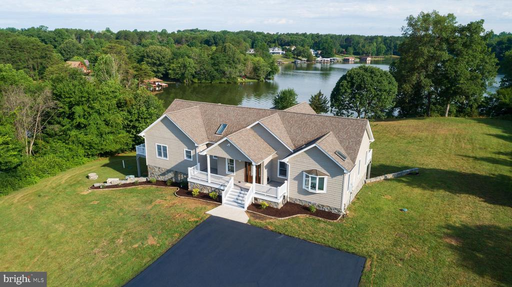 This home will gross in rental income, according to vacasa, between $128,000-150,000/year.  This 5 bedroom, 5.5 bath premier property is located in a non-HOA, 6 house community on the public side of Lake Anna and sits on a 3.5-acre point lot w/ 1000 feet of private and deep (20'+) waterfront.  This large property provides ample privacy.  There are 2 oversized and well-appointed boathouses with lifts (3 boat, 4 waverunner) and private boat ramp.  Boat house 2 is complete with a gazebo, comfy outdoor sectional sofa and an outdoor kitchen with granite countertops for cooking the best scrambled egg breakfasts during the summer and having a chili cook-off during fall seasons. Each boathouse contains commercial Hoshizaki ice machines for quickly icing down a boat for the day on the lake or hosting a party. Why go out to dinner when the boathouse kitchen provides waterfront dining with no waiting! The shoreline has a naturally sandy beach.  There is also a 90 AMP Tesla charger for electric car owners!   The very private and lovely 1-mile road to the home is shared with the 6 homes in this community and is a great place to get your steps in!    Let's not forget that the 2 YAMAHA WAVERUNNERS AND 1 BOAT (YAMAHA JET BOAT AR 230), and JOHN DEERE GATOR can CONVEY with the sale of this home.  Other exterior items are negotiable.  The interior features include custom knockdown textured walls, 5 primary bedrooms & over 4800 finished square feet of living space with a brand new whole-house Netone central vacuum system.  Included on the main level are 2 primary bedrooms, 2.5 baths, dining room with peninsula fireplace, gourmet kitchen with island and gas cooking, large sunroom, and a Great Room with a fireplace.  Other features include 24' vaulted ceilings and walls of windows exposing stunning views of Lake Anna from anywhere in the home. There are 3 fireplaces, an additional complete kitchen in the walk out lower level, & marble appointed baths. Each of the 5 primary bedrooms offer