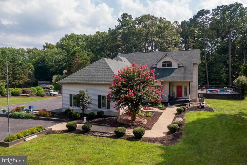 A home that offers the privacy and tranquility of a rural area AND is less than 10 minutes to the beaches of Ocean City, the ponies of Assateague Island, and America's Coolest Small town, Berlin! – look no further for the perfect location! Turn into the community of Cedar Creek and find this 4 bedroom, 3.5 bath property at the end of a private and lengthy driveway. Professional landscaping of trees and fully bloomed flowers leading up to the house gives all that 'welcome home' feeling.    The first level features one bedroom and full bathroom with a slider that leads out to a spacious and secluded screened in porch. First floor also has a foyer, living room, dining room, large kitchen area with an island for extra counter space, and a completely remodeled modern half bath powder room. Improvements include new luxury vinyl flooring throughout the first floor that includes foyer, living room, dining room, kitchen, half bath and fresh paint throughout.  Many large windows and 2 sliders allow plenty of natural light to pour in to every room of this home. Venture out of the back sliding doors to fresh air and an open, oversized patio deck, which includes a hot tub and an outdoor pool (only 3 years old). Pool area is safely fenced in, with trees and landscaping surrounding for privacy. This Peaceful back yard area leads all the way to a creek and has plenty of room for boat storage, yard equipment, and more. Backyard also has an outdoor shed for lawn equipment and EVEN more storage.   Second level has 3 bedrooms, 2 full bathrooms, and boasts plenty of storage space with 2 large walk-in closets and an attic storage area. The Master bedroom and bathroom has a full shower, new toilet, and jacuzzi tub.  A feature unique to this home is a huge custom walk-in California style closet, with jaw dropping lighting, plenty of shelves and drawers, upgraded flooring, granite counter top, and another storage attic. Don't forget to push the grey button on the wall to showcase the custom