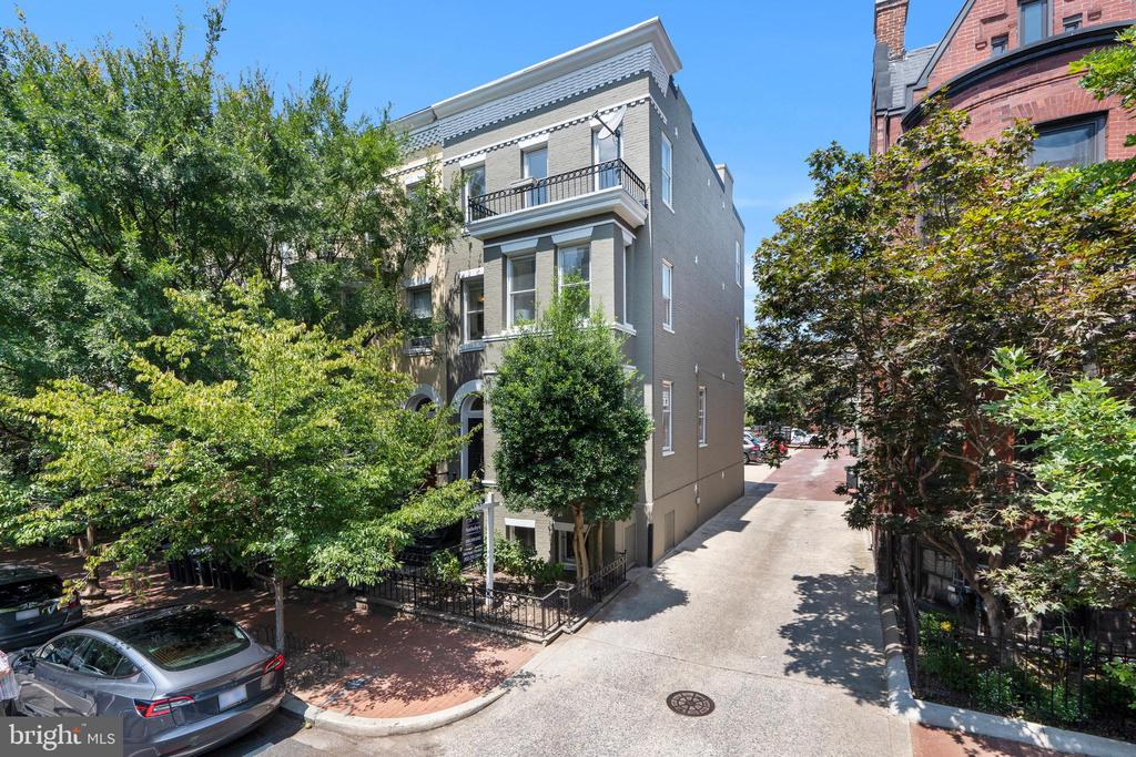 This beautiful semi-detached brick townhouse is ideally located in Dupont and is within close proximity to West End, allowing for convenient access to nearby shops and restaurants of both neighborhoods. The house features elegant period details, attractive crown moldings, four fireplaces, and original hardwood floors throughout. There is abundant natural light from large windows on three sides, which is further magnified by the high ceilings. The main level has a front vestibule that leads to the sophisticated living room with a lovely bay window. The living room opens to a dining area and then to the gourmet kitchen, which offers Carrera marble countertops, a center island, and stainless-steel appliances, including a Sub-Zero refrigerator. A powder room and laundry are also conveniently on this level. The second level includes a light-filled primary suite with a renovated bathroom, ample closet space, and a bay window seating area. In addition to the primary suite, there is another spacious bedroom and a hall bathroom on this floor. Upstairs, there are two more bedrooms, a hall bathroom, office with built-in bookshelves, linen closet, and an attractive skylight. The lower level of the residence acts as a fully separate apartment with a legal certificate of occupancy. It is separately accessed by both the front and rear and includes one bedroom and bathroom, an open kitchen and family room, and a separate laundry. The residence has off-street parking for one-car. The house is within walking distance to neighborhood favorite restaurants, shops, parks, and the Metro.