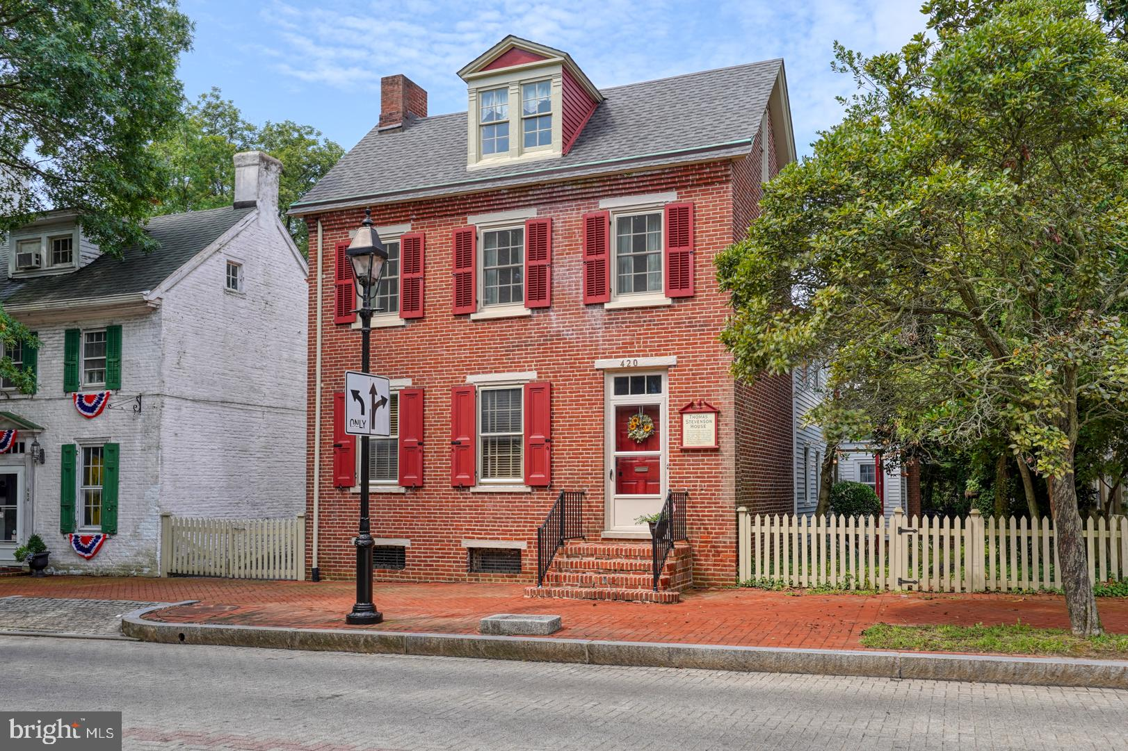Step back in time with this glorious colonial home known as The Thomas Stevenson House.   Situated on a 1/2 acre lot with a park like setting,  the brick home was built in 1846 and was joined with the other structures to the rear of the property that included a summer kitchen and a 2 room schoolhouse.    Located just off of The Green in downtown Dover,  an area that celebrates the history of the state of Delaware.  The home sits on a large property which has a huge park like setting in the fenced backyard.  It can be accessed from S State Street or a private driveway off of W Water Street.   Upon entering the front door the first floor includes a sitting room with a fireplace surrounded by Delft tiles and built in shelves.  There is a butlers pantry directly off of the sitting room.  Down the hall you will find the dining room with another fireplace and a back stairway to access one of the upstairs bedrooms and sitting room.  The cozy kitchen is in the room next to the dining room with another fireplace.  To the rear of the kitchen is a laundry room with half bath.  Directly off of the laundry room is the former summer kitchen and the original 2 room schoolhouse with side door entry and stairs to one room of the schoolhouse.  The entry level of this area could easily be converted to another living area or a first floor bedroom and full bath.   Upstairs there are 2 bedrooms in the hall that share a full bath.  There is also an inlaw suite complete with full bath and sitting area.  Sitting area could be another bedroom.  The sitting area and the bedroom both access the stairwell to the dining room.    There is also an attic space, perfect for storage.   Really unique home that was previously owned by a local historian who lovingly restored it to its original state.  The home has only been used as a residence but the current zoning does allow for office space.   Conditional uses include shops, bakery, B&B, restaurant, etc.