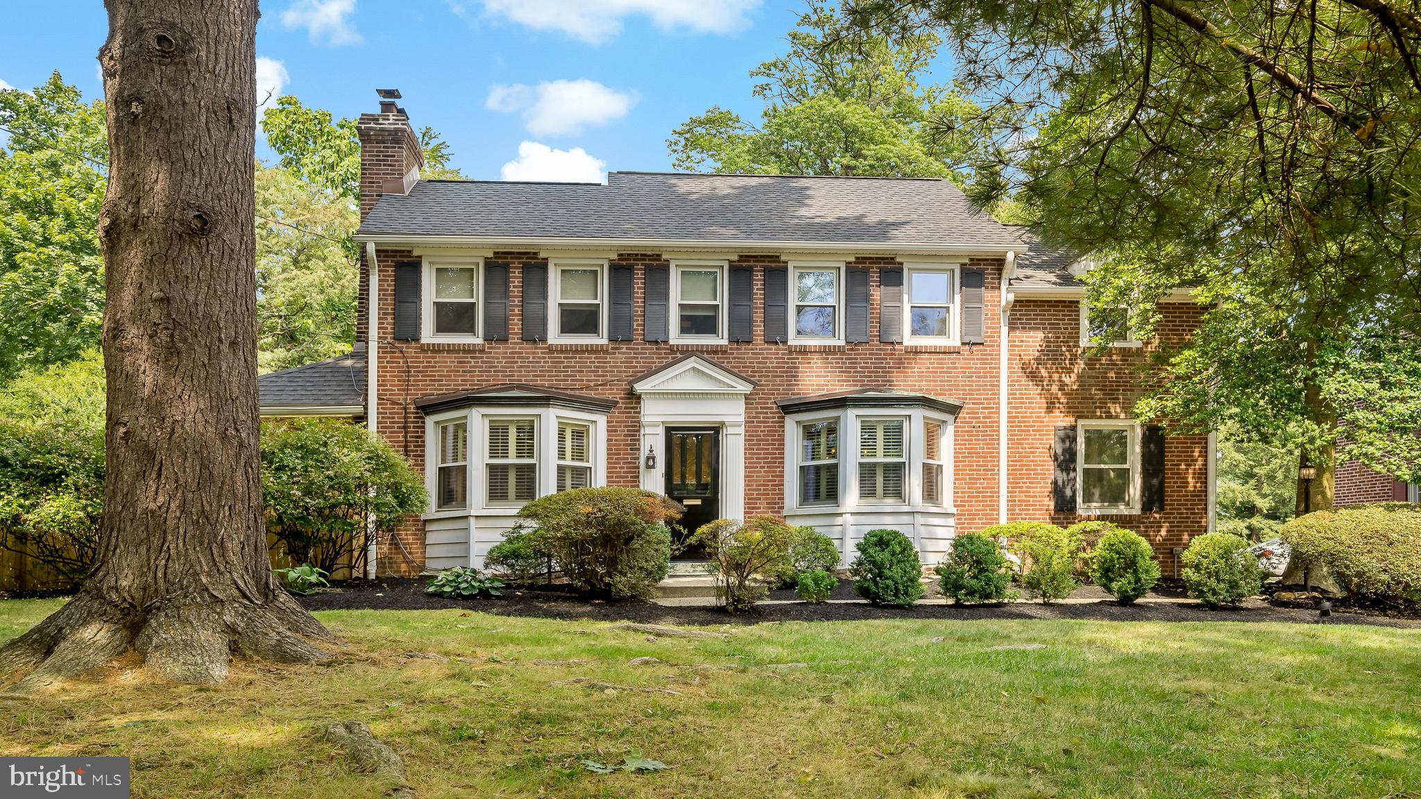Welcome to 1045 Montgomery Ave, where you'll enjoy comfortable, elegant family living in a premier Penn Valley neighborhood. This special home offers a harmonious blend of old and new, with some wonderful preserved original features from the 1940s and many modern upgrades tailored to today's discerning buyer. The classic historic Main Line colonial sits on nearly half an acre of lush private grounds brimming with trees and shrubbery, with expansive level side and rear lawn areas for the kids and pets to play. Lounge outdoors with guests and loved ones on the covered porch and patio, perfect for coffee, cocktails, reading and conversation.   Beautiful interiors boast over 2,300 square feet of charm, light and luxury, with an additional almost 700 square feet in the newly finished lower level. The warm, gracious ambiance is enhanced by rich wood floors, tasteful millwork, crown moldings, high ceilings, and an inviting fireplace. Also setting this gem apart is the thoughtful layout and functionality of space which accommodates relaxed living and easy hosting, with a great flow from the living room to the dining room, granite/stainless steel kitchen, and family room.  Sleeping quarters are spacious and serene, highlighted by a generously-sized master suite with a private bath on the main level and a 2nd original master suite on the upper floor. Both have plenty of room to accommodate a remote office area. The primary owner's suite is king-sized and divine with a desk area, custom California closets, and French doors leading outside. With 4 bedrooms in total, there are many possibilities to meet your family's needs. And then there's the bone-dry basement, an ideal hideaway for all ages with a media/sitting area, exercise room, laundry room and bath.   Your favorite aspect however might just be the location, just a 10-minute walk to the train and a quick 20 minute ride to Center City Philadelphia. Suburban Square shopping is close by as well, as are top-rated Lower Merion