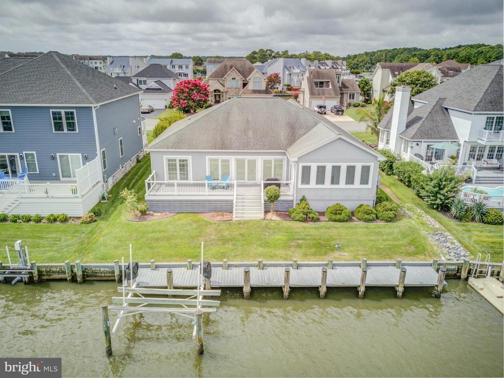 NEW PRICE AGAIN . Dreams do come true! Looking for a waterfront 1 level custom-built home with boat dock and lift with quick access to Bay and Ocean? Look no further. Very large open Living and Dining room with tile floors and lots of windows. Gas Fireplace added and TV included. Sun Room/den directly off that with access to large rear deck with gas grill hooked up to central line. Primary bedroom has a primary bath with walk-in closets, shower and separate areas with twin sinks. Laundry room with Bonus/Office room off to one side and pantry closet for additional storage. Large kitchen with great bar seating plus a desk area and pantry. 2 car garage and concrete driveway. 60 ft. long pier with boat lift.  Nice rear yard. Remaining furniture will stay along with 4 TVs and Surround Sound system. Ready for your enjoyment immediately.