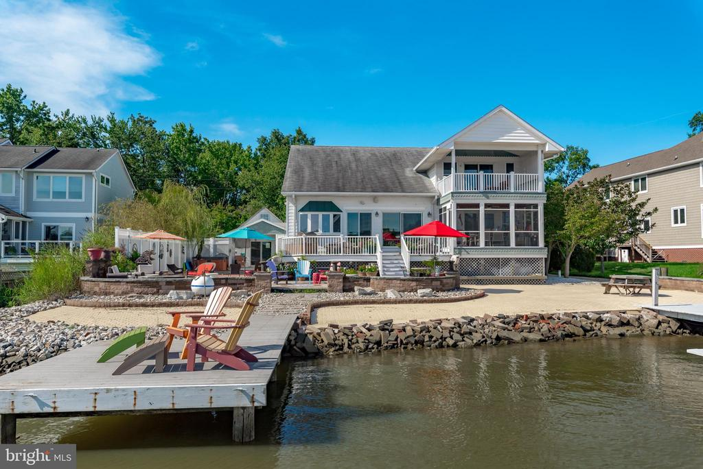 Waterfront and Sunrise enjoyment defines this eclectic cottage on Fishing Creek!  Entertain to your heart's desire and take a dip in your private pool while enjoying activity on the water.  Four-plus feet of deep water on Fishing Creek allows you to have larger boats at your dock.  There are three lifts and multiple slips for a variety of vessel sizes. The boathouse has a newer (2019) roof with leased solar panels. There is a home office  and workroom in the boat house in addition to the covered lift. Everything about this waterside of this property is designed for enjoyment of The Chesapeake Bay! This home connects the charm of a 1940s cottage to a 2004-built, vaulted, great room with wide plank Koa flooring, a floor-to-ceiling gas fireplace, a chef's stove and visual enjoyment of the water from every corner. One main level primary bedroom and a second primary bedroom suite on the upper level.  Rooms for two home offices in addition to four bedrooms and four full baths.  Workroom and laundry on main level.  Custom, curved stair case welcomes you to the primary suite and home office on the upper level. Additional storage in upper level closet and large walk-in closet. Two car garage with storage above it  and covered entry to home.  Side driveway with parking for at least eight cars. Oakwood Community has a voluntary HOA fee of $50/ year with neighbors enjoying frequent trips to Thomas Point Park and seasonal wildlife.