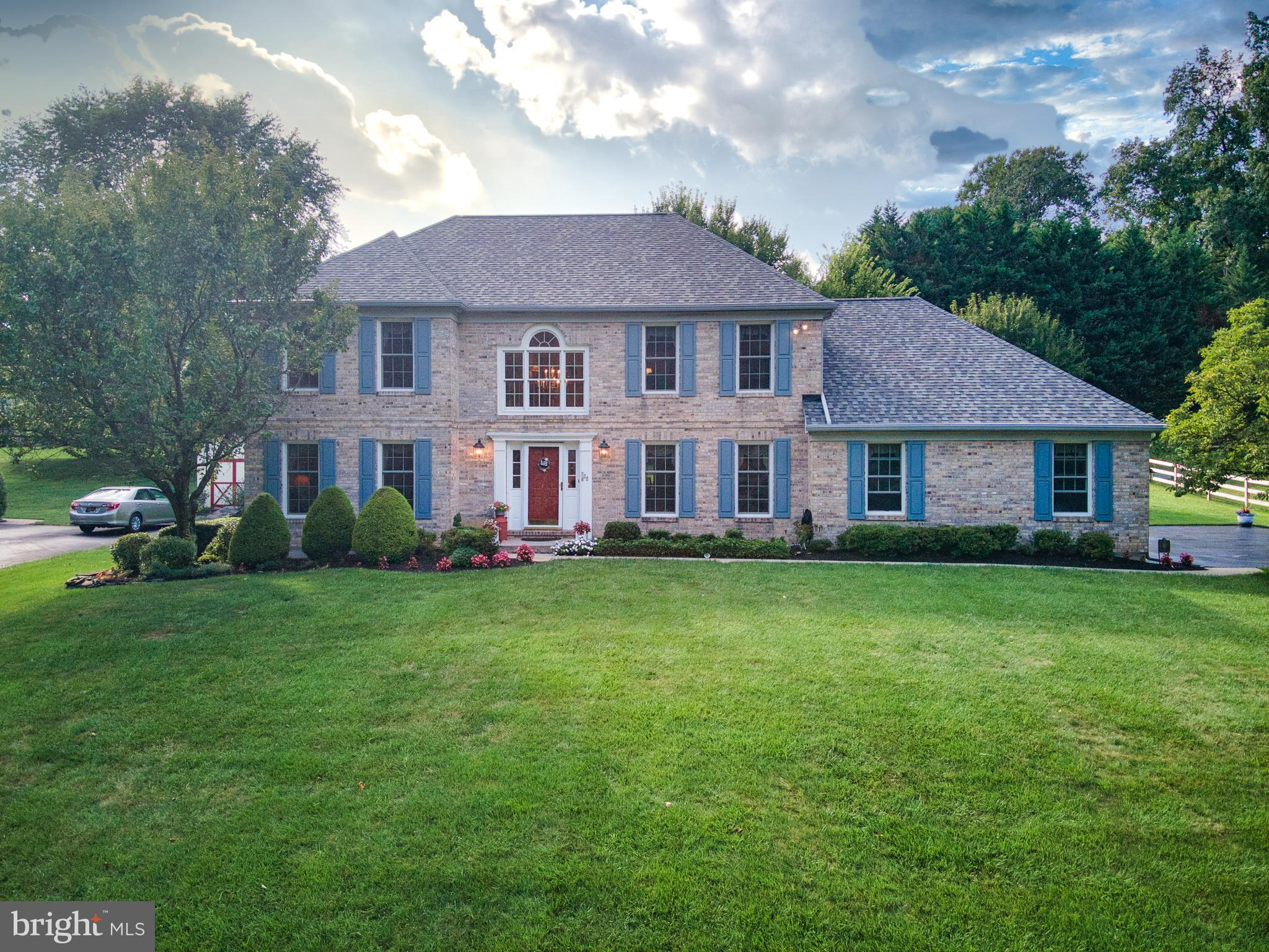 Impeccably maintained, custom built Colonial with spectacular upgrades sits on over half an acre in the hills of Hockessin! On an enviable cul-de-sac surrounded by beautiful landscaping and mature trees, this brick front home is sure to impress. Noteworthy features include an expansive open concept floor plan, a spacious sunroom for year-round enjoyment, and an oversized deck with a retractable awning overlooking the lush backyard. From the moment you enter this impressive home, you will delight in the fine finishes and impeccable hardwood floors that seamlessly flow throughout. The sun-filled two story foyer is flanked by a picturesque formal living room and a formal dining room, with elegant wainscotting and plenty of space to entertain. The expansive gourmet kitchen is generously appointed with tailor-made light cherry cabinets, distinctive granite countertops, stainless steel appliances, dual ovens, and an oversized island with a breakfast bar, sure to delight chefs and hosts alike! A custom butler's pantry offers additional storage adjacent to the eat-in dining area with sliders to the back deck. The open floor plan continues to the spacious family room which features a cozy gas fireplace flanked by large, sun-filled windows, perfect for family gatherings every holiday season. French doors open to the stunning 17'x17' sunroom. Walls of windows and four large skylights flood this room with natural light. Offering Italian tile floors, a wet bar for entertaining, and a ceiling fan, this room is prime for your enjoyment and leisure year round. The main level of this stately home also features a service hall that leads to a large tucked-away laundry room, convenient access to an oversized two-car garage with built-in shelves and newly refinished flooring, and a private home office with custom, built-in cabinetry and wainscotting. A powder room for guests completes the first floor. The striking staircase leads upstairs where hardwood floors continue throughout the ha
