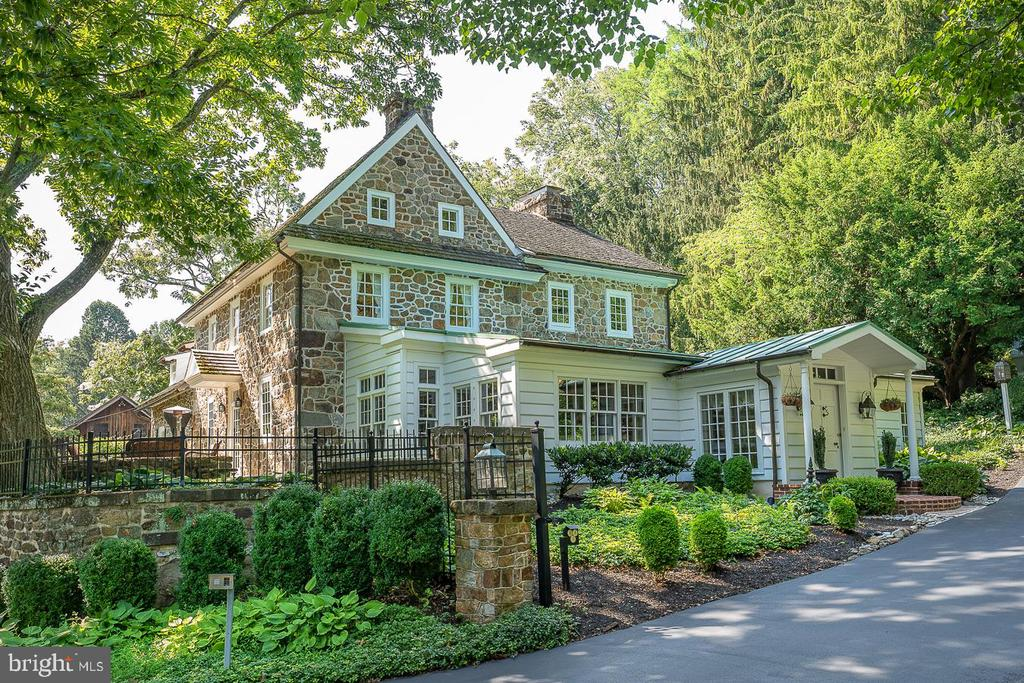 One of the most admired homes in Chester Springs, this magnificent stone home, built in 1740, sits high up on 6.8 acres, consisting of 2 parcels. There is a great sense of privacy, tranquility & history behind the gated entrance, where you will experience a world apart, one of uncompromised taste, charm and quality details in every room. You can expect the unexpected in the flow of rooms, from the front great room with a stunning, entire exposed stone wall, (previously an outside wall) the floor is made from bricks (that have been glazed) from Philadelphia, & includes 3 zone radiant heating. There are 7 heating zones and 3 AC zones. Unlike many older homes, this room, as do most others in this stunning home, offers high vaulted ceilings w/ beams, indirect lighting fixtures and walls of windows that take advantage of the wonderful Southern exposure. The flow for entertaining is fantastic & all of the floors are wide, random width and gleaming.The kitchen, which features high end cabinetry, Bosch, Sub Zero, Thermador & Miele appliances & great storage space, opens to a dining room/ area with fireplace & openings to the fabulous wet bar room, which can easily sit 12+ for an extra dining room…cozy up to the fireplace, enjoy cocktails, or take your morning coffee to the slate terrace & relax under the Chestnut tree! Follow thru to a perfect office space, with walk in fireplace & enjoy overlooking the pool w/hot tub, with beautifully planted brick walkways surrounding the back of the home, plus patio for outdoor living Bonus…the home is Technology savvy! There are 4 corporate grade Wireless Access Points & a Sonos wireless sound system in 5 areas of the home & 1 for the pool area. A beautiful curved stairway takes you to 2-3 charming bdrms on the 2nd flr with 2 enormous custom closets & oversize primary bathroom. Enjoy the sound system in these rooms as well. On the 3rd fl is another bdrm w/vaulted ceiling, beams, beautiful windows with deep window sills & a cedar closet 