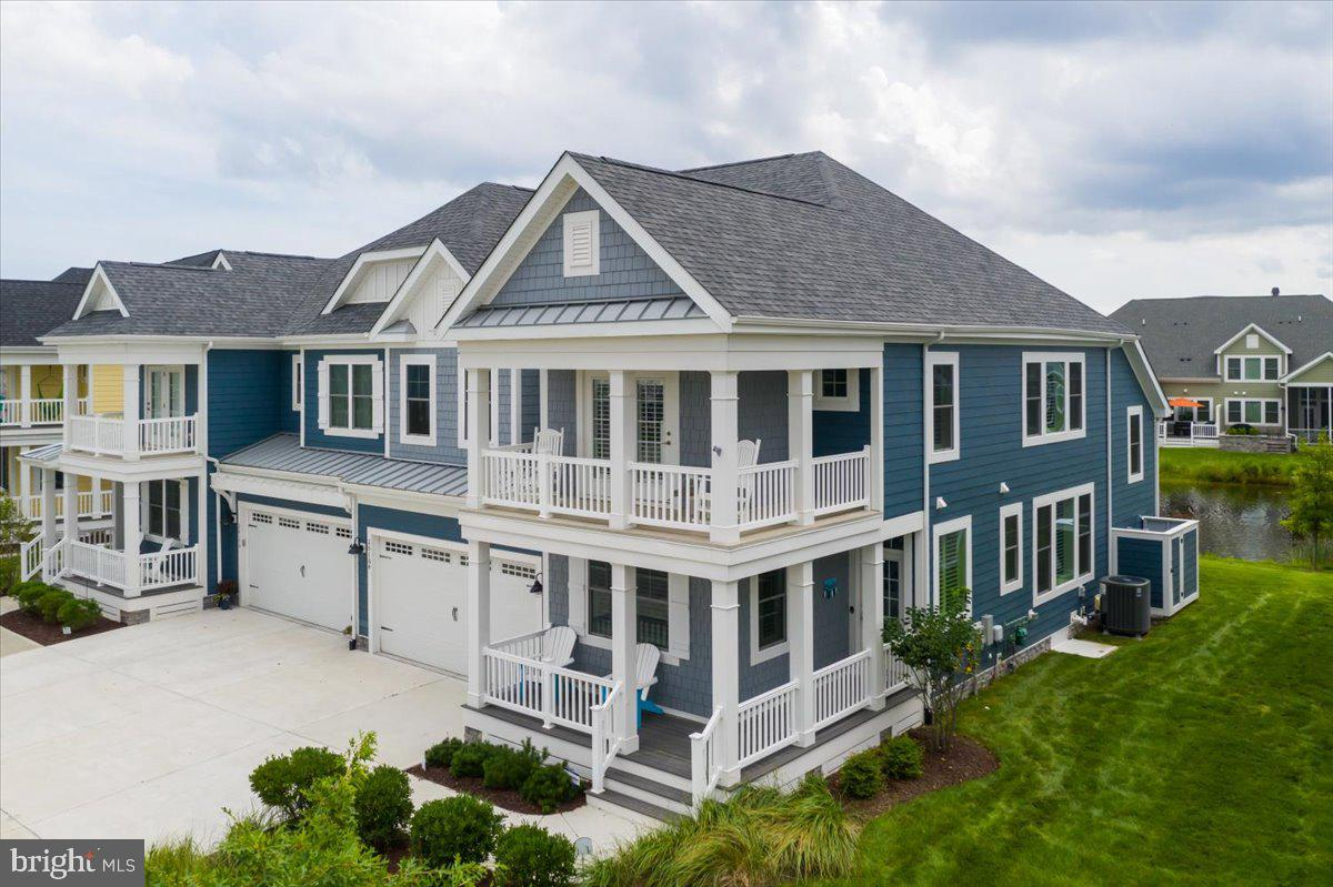 """This 4 Bedroom 3 1/2 Bathroom Hatteras floorplan built by Schell Brothers offers a stunning location on a wide pond in addition to featuring views of the Jack Nicklaus golf course.  Approaching this home you will take note of the wrap around front porch on the first level as well as the wrap around balcony on the second level.  Enter through the spacious foyer draped in designer wall paper.   Directly off of the foyer is a large office as well as a first floor laundry room / mudroom which leads to a 2 car garage.  Moving further into the home a half bath for visiting guests includes a custom sink cabinet and plantation style window shutters that are installed on the majority of the windows in the home.  The gourmet kitchen includes a glass tile backsplash, stainless steel appliances and farm sink, and quartz countertops.  Gathering with family and friends will be effortless as the kitchen features plenty of seating and boasts a double wall oven and beverage fridge.  Around each and every turn you will be """"Wowed"""" by custom upgrades in this home including millwork such as the built-in cabinets surrounding the gas fireplace as well as stylish light fixtures and ceiling fans.  The grand living room with a wall of windows and towering vaulted ceilings offers a calming view of the wide pond with multiple fountains.  From the living room access the oversized screened in porch which leads to a private outdoor deck.  The backyard offers plenty of green space for activities.  Back inside enter into the serene first floor primary suite that includes electronic blinds, designer wall paper, and two walk in closets.  Also upgraded, the primary bathroom has an oversized tile shower with built in bench and four wall jets.  Your tour continues as you arrive at the second floor after passing over a large landing halfway up the staircase that could be used as a second sitting area or office area.  Here you arrive in the gigantic loft that could satisfy a multitude of living options an"""
