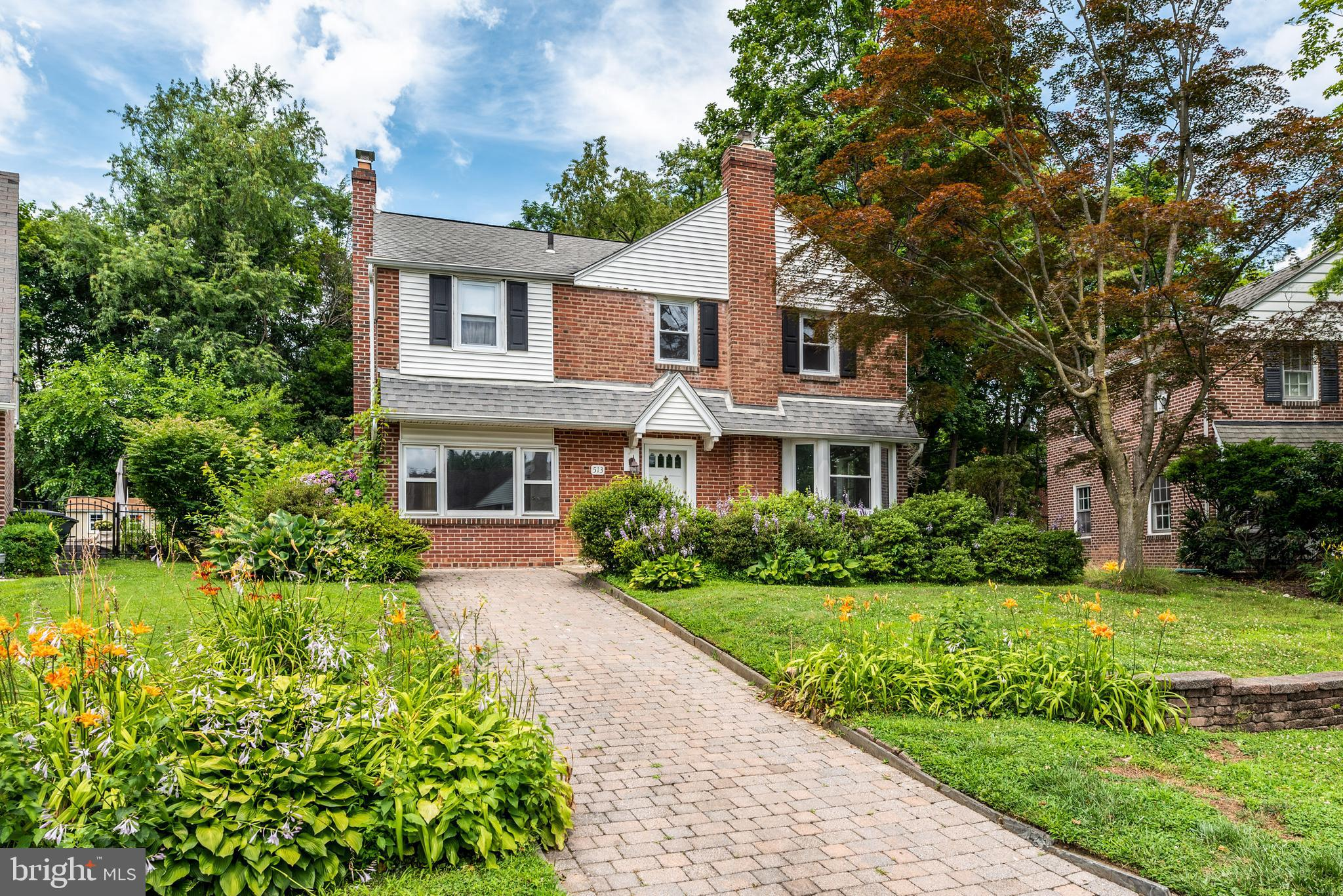 This classic brick colonial is ideally located in the heart of Wynnewood. Within walking distance to schools, parks, and shopping, Rock Glen Drive is a pretty street with nice front yards and a community appeal. This well-loved home is ready for the next owners to create their own wonderful memories. From its access to the top schools of Lower Merion, to its walkable streets and easy commute to Center City via the Regional Rail, there is so much to love! From the pretty entrance, enter into the living room, with wood floors, deep-silled windows and attractive, classic feel. A charming, arched entrance leads into the dining room, also with hardwood, chair rails, and wide windows. Directly off the dining room is the enclosed, generous sunroom, with views of the wonderful backyard, perfect for morning coffee, birdwatching, or cool, early fall suppers. The dining room leads into the kitchen, with cheerful white cabinetry, nice backsplash and tile flooring. The first level also features a den with fireplace; a powder room is located off this room. The second level has three attractive bedrooms, each with hardwood floors. The main bedroom, with an ample closet, well-placed windows, and a ceiling fan, also has a full bath with stall shower and nice floor. The two additional bedrooms share the hall bath, with a tub/shower combination with ceramic tile and a classic black-and-white tiled floor. The lower level/basement is clean and neat, with plenty of room for storage. The backyard is a real gem: lush, level, and absolutely perfect for entertaining throughout the seasons! Rock Glen Drive is an attractive, welcoming block in a top-tier township—with so much to recommend it, it is well worth the investment. This lovely Wynnewood neighborhood has walkable streets and is great for jogging. It is very close to Suburban Square, with its fantastic farmers market and delicious restaurants, as well as a variety of sought-after shops. Whole Foods is also close, as are Wynnewoods beau