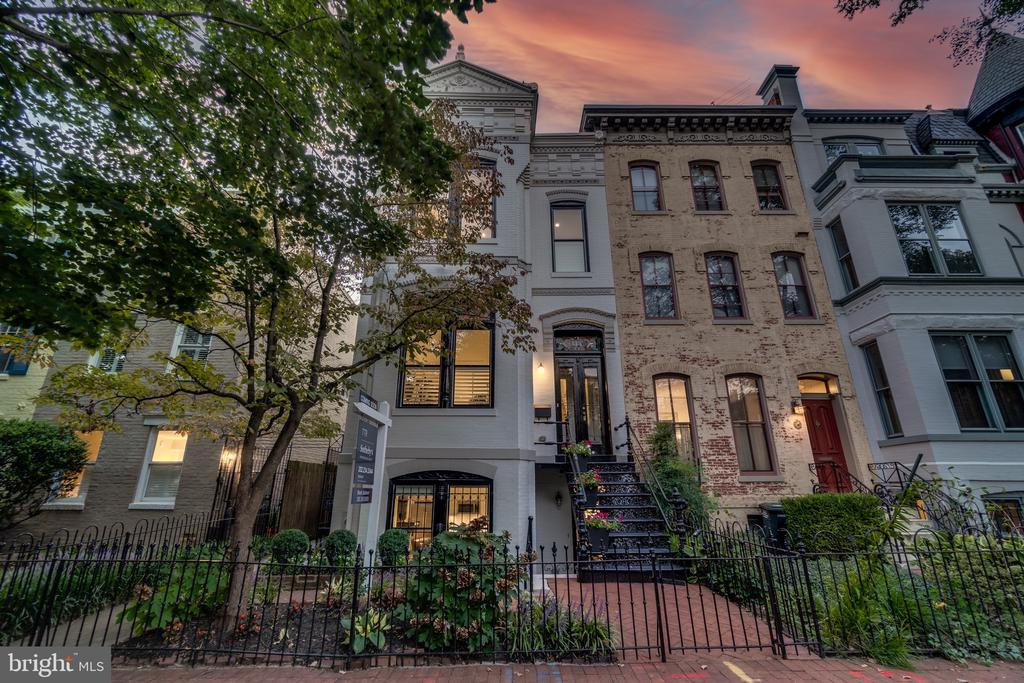 Welcome to this jaw-dropping, impeccably renovated, semi-detached Queen-Anne rowhome on a 24-foot-wide lot, set on a prestigious Capitol Hill block! In the shadows of the US Capitol and a short stroll to the Library of Congress, located in the Brent Elementary school district! This 5 Bed/3.5 Bath home spans over 3,000 square feet with 11-foot ceilings, two fireplaces, multiple bay windows, and a separate two-car garage. The open plan main level is an entertainer's paradise, featuring an expansive living area, herringbone oak floors that continue through the dining area to the show-stopping gourmet kitchen. Made for a magazine, the kitchen is a chef's dream and features an expansive workspace and breakfast bar. The stainless steel appliance suite and quartz backsplash are a match made in heaven for photo-worthy meals. Wall-to-wall glass doors behind the kitchen open from the dining area to a deck and private courtyard. Upstairs, the large primary suite is graced with excellent natural light, ensuite marbled bath with claw foot tub, and a massive walk-in closet. The second bedroom offers no less grandeur with a two-story loft and a large closet. The upstairs third bedroom is also spacious in size and both bedrooms share an additional bathroom with a similar luxe finishes. The fully finished in-law suite located in the basement boasts a second open plan living area with kitchenette, as well as two additional bedrooms and a full bath. Solar panels complete this amazing offering. This premiere location is a few blocks from Eastern Market, Barracks Row, Brent Elementary, Metro, and so many restaurants, shops, cafes, and bars, along with Trader Joe's grocery just down the street!