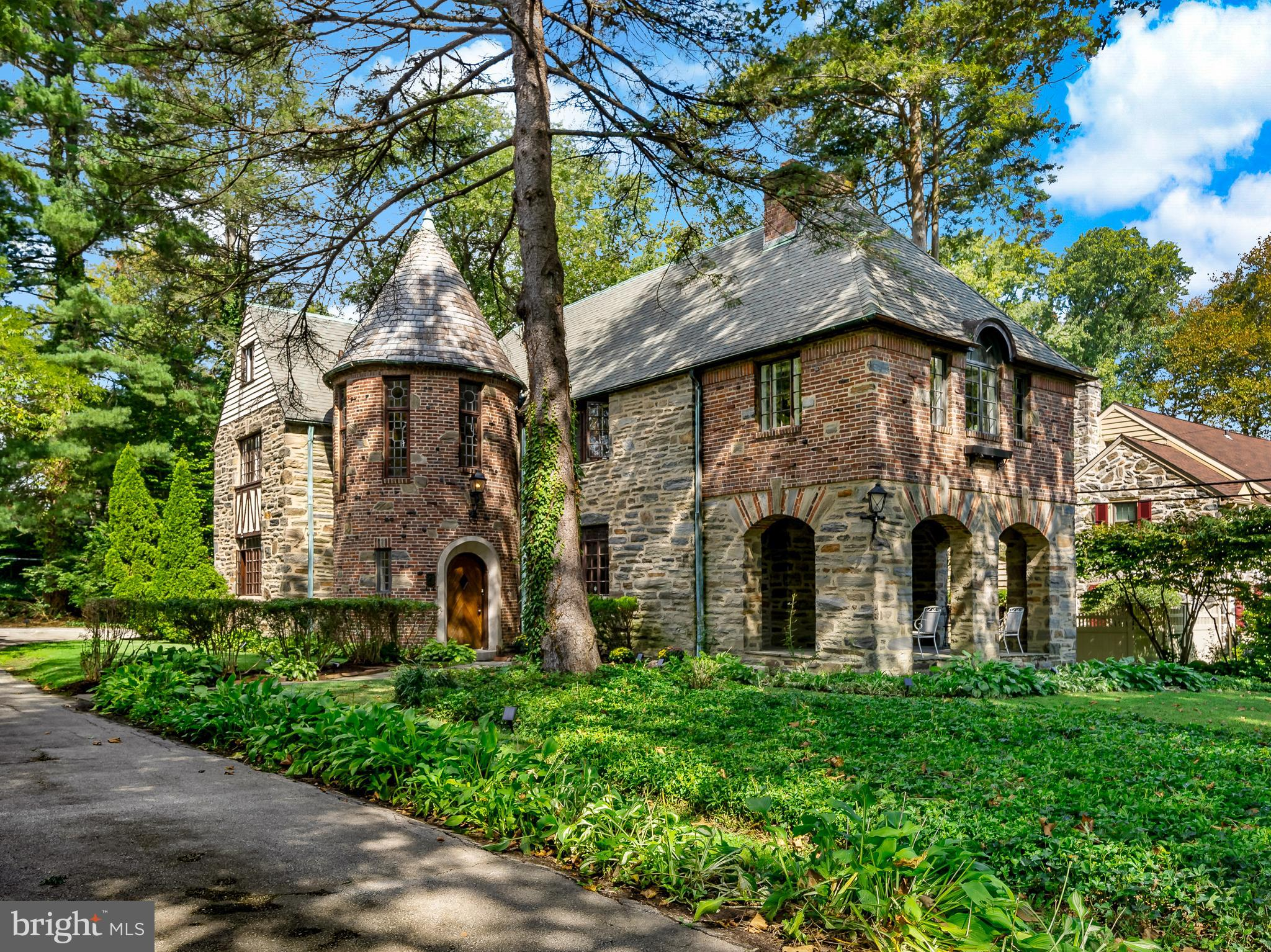It is impossible not to marvel at the unique architecture and endless potential of this enchanting French Norman style home by architect/builder Henry D. Dagit & Sons. Filled with original features, such as its castle-like turret with grand curved staircase, unique wood beam ceilings, Juliette balconies, French doors, stone and hardwood floors and three beautiful wood burning fireplaces.  It is located in the safe, friendly and walkable neighborhood with easy access to the city; 1309 Morris Road is located in the Minden Manor area of Wynnewood, and gives you old-world charm with modern day conveniences.   When you enter this home, the foyer leads you to a spacious, light-filled living room with timeless, elegant features like the wood beam ceiling, built-in bookcase, coat closet, hard wood floors and an exquisite crested stone wood-burning fireplace. From the living room, walk directly through the French door onto the covered flagstone porch used throughout the year. To the left of the living room is the formal dining room, with doors leading to a Butlers pantry and into the eat-in kitchen, the perfect place to host all your grand holiday parties. Off the kitchen, you will find a mudroom/pantry, the laundry room and direct access to an attached two-car garage.    In the turret, a small powder room is located under the curved staircase with a wrought iron railing, which leads you to the second floor. Here you will find the primary bedroom, which boasts hardwood floors, a wood-burning fireplace, a large deep closet, charming Juliette balcony, and a separate sitting/dressing room with additional closet space and private full bath. Also on the second floor, there are 3 other bedrooms with hardwood floors, one of which also has a Juliette balcony. Two of the bedrooms share a bathroom and the other has its own private full bath.   A back hallway leads you to 2 other rooms that can be used as a quiet office space, exercise room, a cheerful playroom, or as additional bedroo