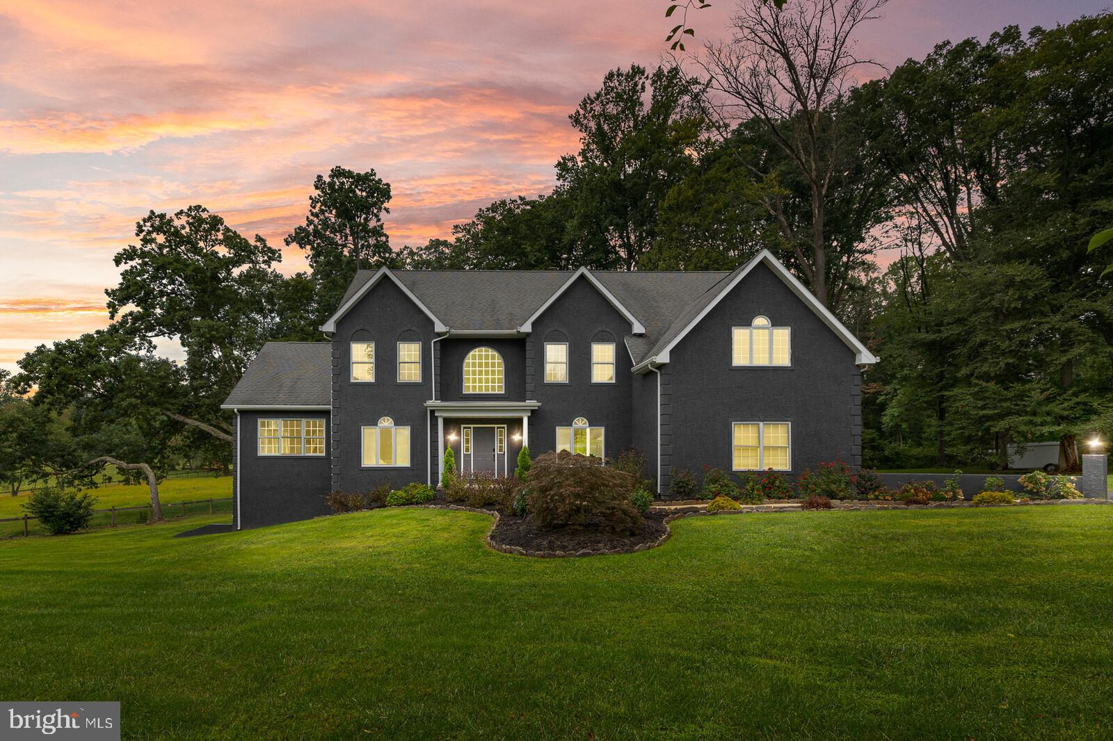 Watch the sunset every night over the rolling hills from the back deck of this uniquely designed custom home.  This home has been renovated from top to bottom with dark tones, hand selected finishes, a two story custom double sided fireplace, along with TV's included. Voice activated recessed lights are installed throughout the home to be used with Alexa.  The main level has a beautiful sunroom that opens up to the deck with lots of natural light flowing through.  The sitting area in the kitchen is perfect for coffee in the morning while you relax in front of 60+ acres of farmland and preserved land. The Owner's suite has vaulted ceilings and an extra large bathroom with a jacuzzi tub, two vanities, a stand up double headed shower, and four walk-in closets.  There are two laundry rooms with one next to the Owner's suite and one in the basement.