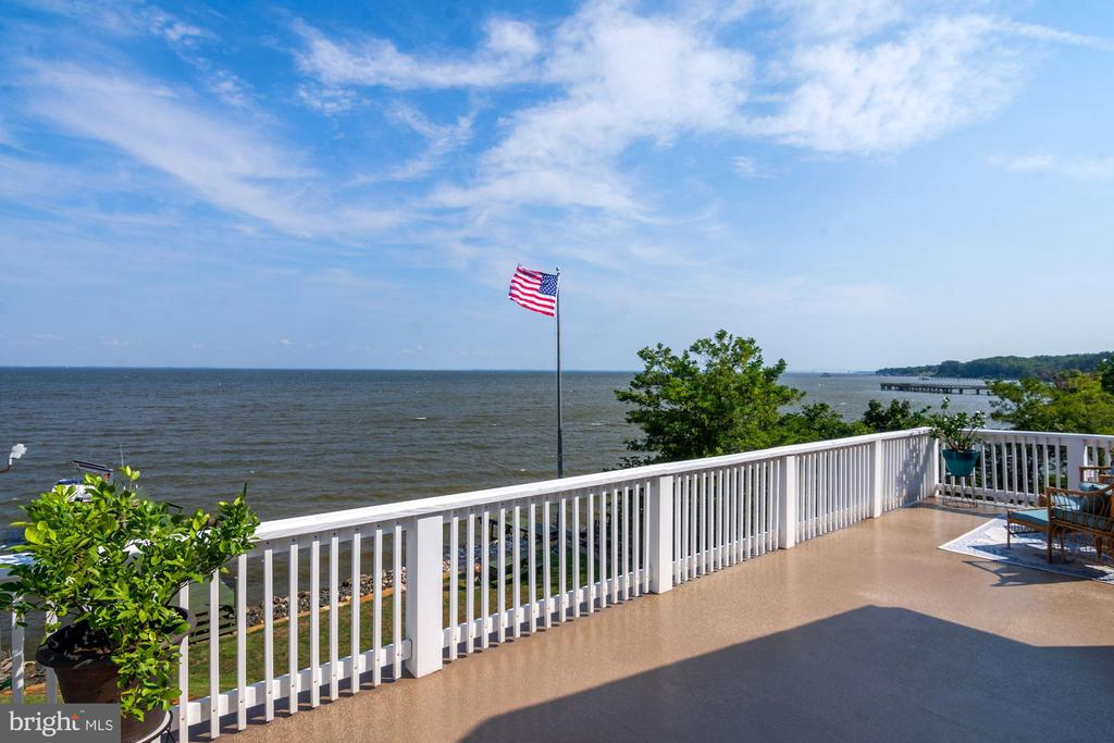 """Get the BIG BAY VIEWS you've been looking for!  This beautiful waterfront home was one of the original cottages built in the 1920's (tax record says 1948 because that is when the first tax record was recorded on the property).  It's been renovated and structurally reinforced, with vinyl siding, a new roof,  dual zoned A/C,  lower level finished to include an additional kitchen, and installation of a French drain under the lower level.  With all this, the home still maintains touches of the original woodwork and expansive views of the Chesapeake from every level of the home.   This is a  home has been loved through the generations and has been rebuilt to be loved for many to come.  You've found the perfect place to let go of the cares of the world as you enter your dream waterfront home and leave everything from the outside world  in the welcoming foyer, then move into the main area of the house where you can get a refereshing beverage from the kitchen and slide right into your favorite chair to kick up your feet and enjoy the views through the wall of windows showing you the Bay and all it's beauty.  This level also has a bedroom (or office - your choice) and a full bath.   The upper level hosts two bedrooms and a full bath.  One is  a primary bedroom with a private balcony and large bay views.  The Lower Level of the home has a beautiful 2nd kitchen, full bath, sitting area with large picture windows to enjoy the view and your fourth bedroom with views of the water and a large closet.   BONUS!  This level can be separated from the top two levels to create a   living area - can you say """"rental income"""" or """"Guest Suite""""?  There is ample storage on the lower level  (appx 300SF) plus a cute shed on the street side of the home.   You may walk right out your back door - where you have a choice to make:  1) Sit on your patio and enjoy the sound of the water while you watch the ships go by,  2) Step onto your 90 ft. dock and take your boat out to enjoy the waves or 3)  Spen"""