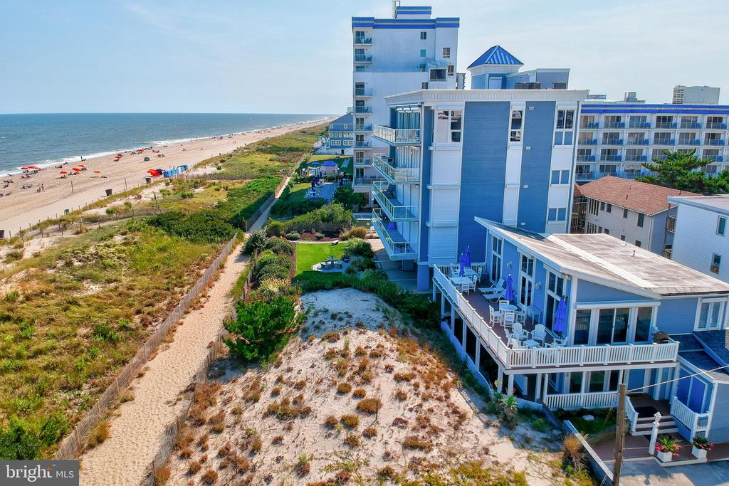 This iconic single family direct oceanfront home is truly a unique offering! This home features 4-5 bedrooms, 4 beautifully updated baths, three of which have double sinks, all include tile flooring, granite countertops, and custom ceramic tiled showers. The first-floor primary bedroom is a true oasis with a private bath, lovely sitting area (which could be used as a fifth bedroom), and two additional bedrooms perfect for guest, could comfortably sleep up to 10 people on the lower level. The lower-level deck has a bench swing to enjoy the cool ocean breeze, extensive landscaping, and privacy fence from the sand dune. Home also features an owner's suite on the second floor with an open floorplan for entertaining. Second floor boasts vaulted ceilings, large floor to ceiling windows which allow an abundance of natural light, living and dining area with four access points to the wrap around oceanfront deck. Enjoy preparing a meal in the gourmet kitchen or relax with your morning coffee and enjoy endless sunrises over the Atlantic Ocean. Small, fenced side yard with a stone patio and beautiful landscaping. Private outdoor shower and wash pad perfect for the long sandy days on the beach. Home has a large walk-in crawl space that is essentially a basement perfect for additional storage, including your beach bikes! Less than a mile to transportation, famous Ocean City restaurants and shopping. Property does have redevelopment potential approved for 3 units under R-3 zoning. Oceanfront living at it's finest!