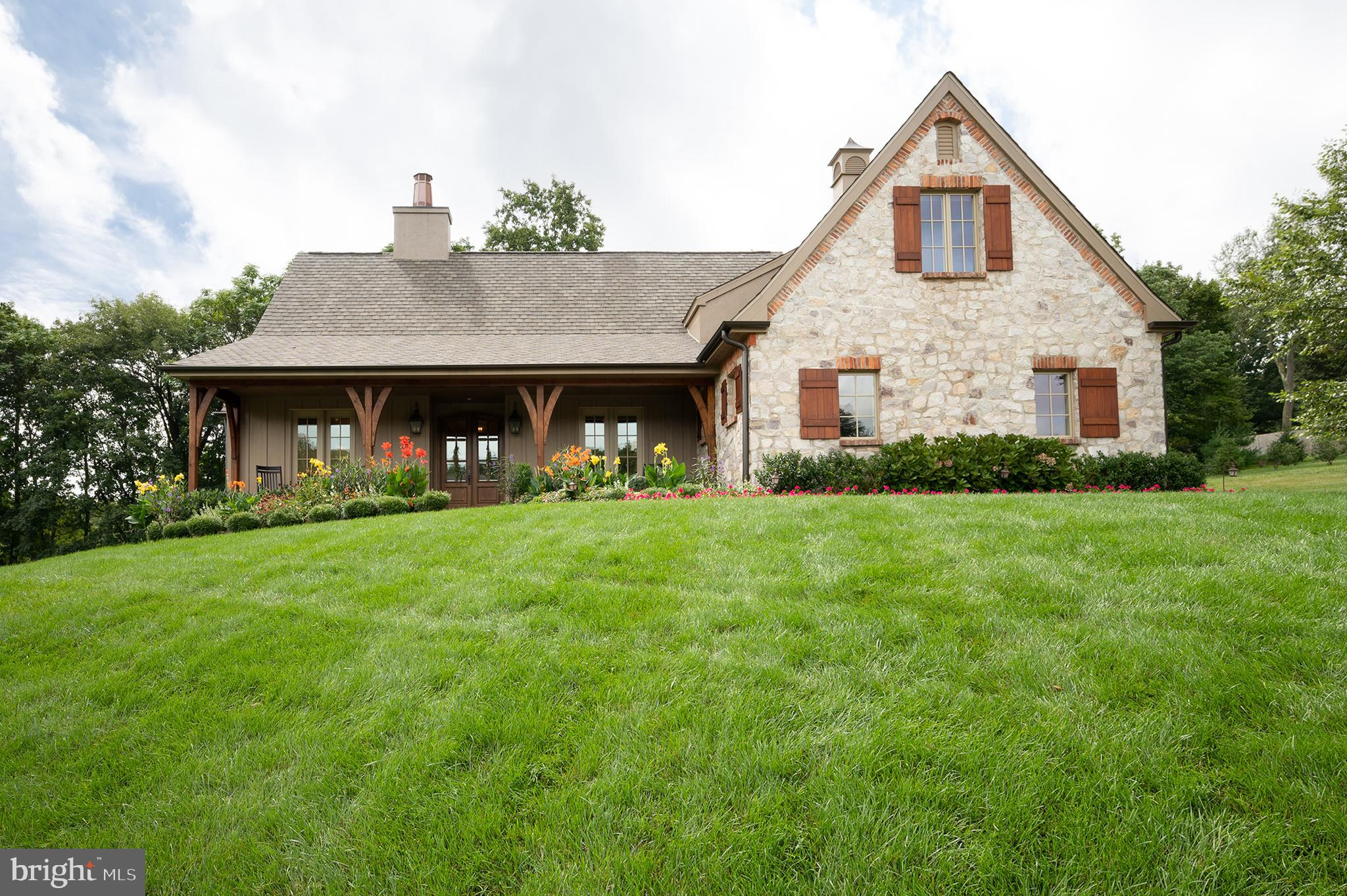 Located on a prime lot in Wagoner's Row, this beautiful residence enjoys an abundance of open vistas, woods and pond views. Created with total relaxation in mind, the architecture, landscaping, and interior design are seamlessly fused together. Exposed beams and volume great room ceilings are light and welcoming, the airy, open-flowing great room linking flawlessly with a modern kitchen. On the first floor the residence comprises an entry foyer with custom appointed hardwood flooring, leading to the open great room, chef kitchen with center island & built-in appliances, separate breakfast room, laundry and main level primary suite with private bath, custom fit-out walk in closet and sitting room. Additional main level features include a 2nd bedroom, main bath, laundry and two-car side entry garage. The upper level includes a 2nd primary suite with a well-appointed private bath, and two walk-in closets. Exceptional outdoor entertaining from the covered porch with roll down electronic screens leading to the open terrace appointed with an outdoor kitchen, overlooking the private-well landscaped setting. Additional highlights include a custom designed stone/brick fireplace wall in the great room, Vantage house automation system, electronic shades, heated flooring in the primary suites, brick herringbone walkways and a full un-finished lower level.