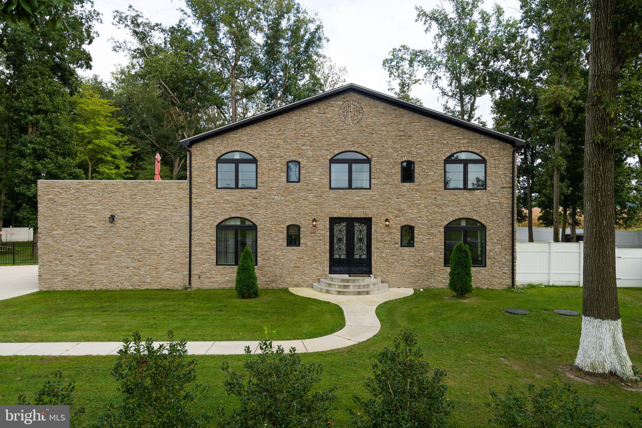 Magnificent Mediterranean-style home in Milton! Set on 1-plus acre of lush, well-groomed property just on the outskirts of historic Milton is this impressive custom-built 3BRs/2 ½ bath over 2,600 sq. ft. stone home. Built in just 2017 this young-aged home is replicated from homes in Spain, and boasts stone exterior, arched windows, and open, sun-drenched terraces. Winding sidewalk carves through level front lawn and leads to circular steps and open entry. Cone-shaped evergreens anchor either side of front porch. Grand wrought-iron filigree doors with bordering windows grant access to ceramic tile foyer and wide-open space, where bench or hutch is certainly at home and rich, turned staircase is just beyond. Enjoy sprawling main space living in this exceptional home. 2-story great room is extraordinary with its massive floor-to-ceiling Northern eastern cedar gas FP, where all can gather for pre-dinner snacks and post-meal chats. Elongated windows flank FP and work in tandem with glass sliders to offer ample natural light. Room size is substantial and allows for easy placement of plentiful furniture and accessories. DR is just beyond and seamless to great room with glass sliders gracing back wall and beautiful wrought iron chandelier commanding attention. DR is completely linked to chef's kitchen where all is at one's fingertips! Ceramic tile floor grounds the room while subway tile backsplash is breathtaking backdrop for smooth maple cabinets. Upgraded countertops are perfectly paired with SS appliances. Substantial island takes center stage and features wrap around countertops which allows for bar stools to be tucked under, ideal for casual snack or sit-down meals. Custom light fixtures bathe this gourmet kitchen in luxury! Barely-there pocket doors with frosted glass inset grant access to charming, sun-infused retreat area of rich hardwood floors. The combination of oversized windows, glass sliders and arched windows together create sunroom effect with natural light