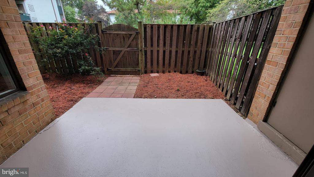This is a  rare opportunity to own your own home near all the best dining, shopping, and entertainment that Northern Virginia has to offer. Clean, safe, comfortable, with updated appliances and bathroom.  This  generously sized ground level apartment even has a fenced-in, freshly mulched yard, and freshly painted patio adjacent to  the shared garden and grill area. PERFECT FOR ENTERTAINING. Full size washer and dryer, huge walk-in closet in a large master bedroom, brand new sliding door and light fixtures, recessed lighting and even your own storage space, for large items.  For those who commute this home is surrounded by major commuter routes.  The community amenities include  a huge gorgeous pool, tennis courts , tot lots, grill areas, and ample open green space. This rarely available move-in ready condo will not be available for long.