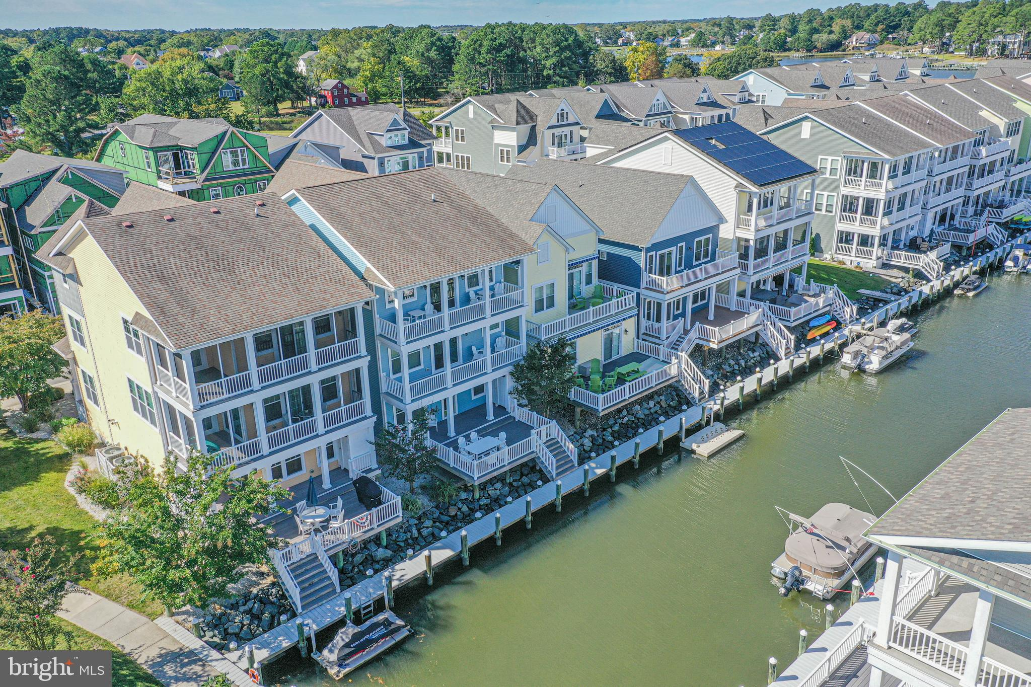 Coastal living at its best! Spectacular former model waterfront home features many fine upgrades, boat slip/dock at your back door.  All of the floors have an elevator, including the top floor with an open floor plan with kitchen, dining, two primary bedrooms, and a covered porch. The second floor has three additional bedrooms, including the 2nd primary bedroom. The first floor has a large recreation room (easy to convert to a 5th bedroom), laundry room, full bath, and a covered porch with a shower overlooking the water. All of the decks were replaced with DecTech in 2020. Sunset Harbour offers a maintenance-free community with a pool, clubhouse, boat ramp, and only minutes to the beach. Easy access to the Indian River Bay and the Ocean.  Home is being sold just as you see it with everything included, no exclusions. Just unpack your bags.