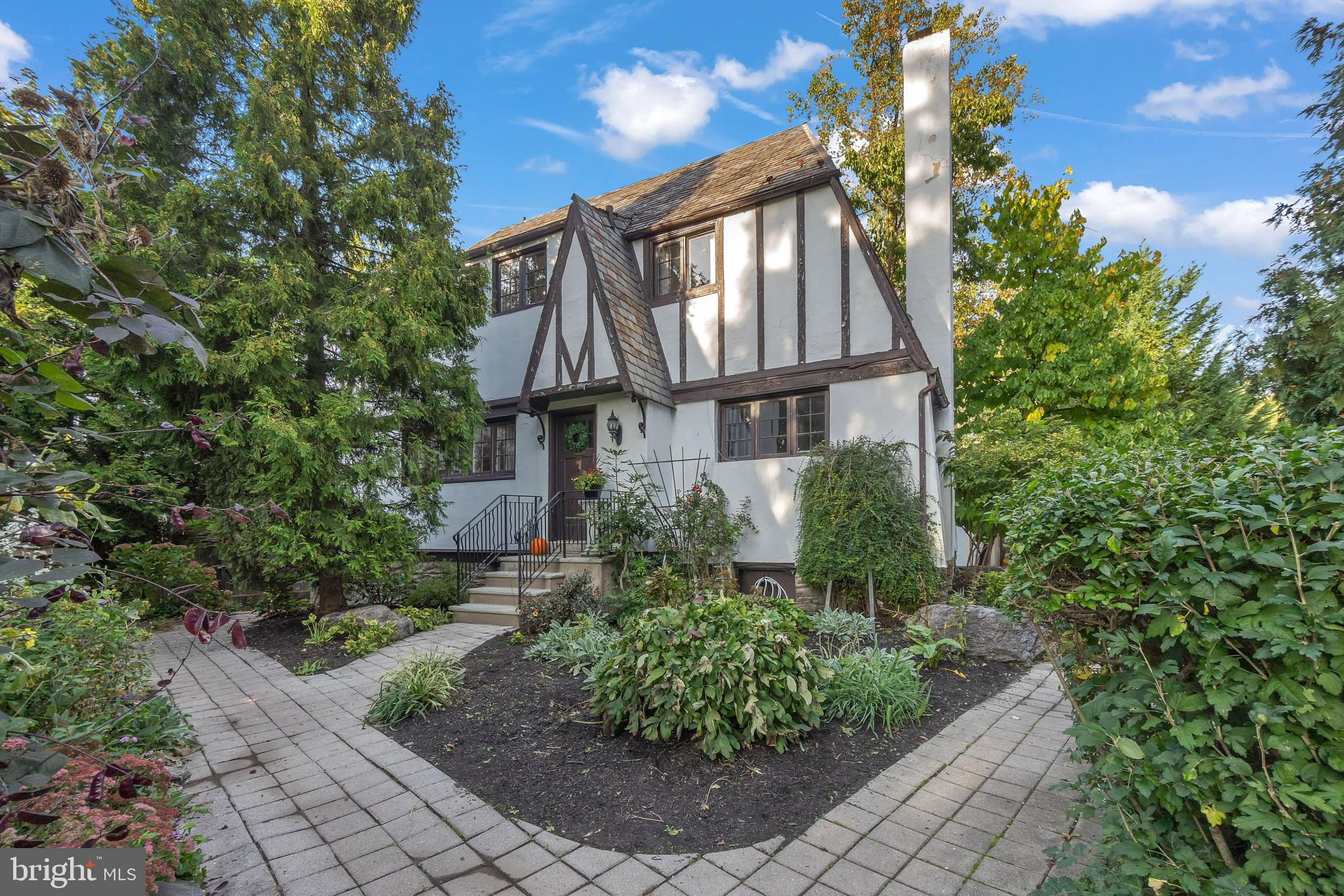 This bright and sunny English Tudor cottage is filled with charm and located within the tucked away community of Balwyn Place, situated off of Bala Ave with close proximity to Philadelphia, and within award winning Lower Merion school district. This charming collection of 8 homes were built in the mid-1920's, originally serving as an artists community.  As you enter this corner property through the beautiful front courtyard, you'll instantly be greeted by vibrant English gardens showcasing a gorgeous medley of perennials and fruit trees.  Enter through the front door and take note of rich hardwood flooring throughout the home. The first floor features a tiled entryway with coat closet and a spacious living room with a beautiful wood burning fireplace and original stained glass window to the staircase. There's a separate dining room with a built-in glass cabinet, perfect for additional storage while entertaining. There's a reading nook adjacent to the dining room, which would also make a great home office area. French doors open to a peaceful deck (installed 2017) with a beautiful Wisteria tree, providing both shade and privacy.  The kitchen features elegant black cabinetry, stainless steel appliances, remarkable copper countertops, state-of-the-art wine refrigerator, lustrous slate floors, and gas cooking. There's a large pantry closet for additional storage. There's a powder room off of the kitchen along with a rear exterior door providing access to the back of the property, garage and driveway area. The second level features a spacious main bedroom with two closets, a generous sized hall full bathroom with shower/tub, and two additional spacious bedrooms with beautiful windows and tons of natural light.  This cottage home boasts a full sized, unfinished basement with a walk-out exit to the exterior and a laundry area with a utility sink and shelf storage. There's a walk up third level attic with potential to be utilized for storage or finished to serve as added li