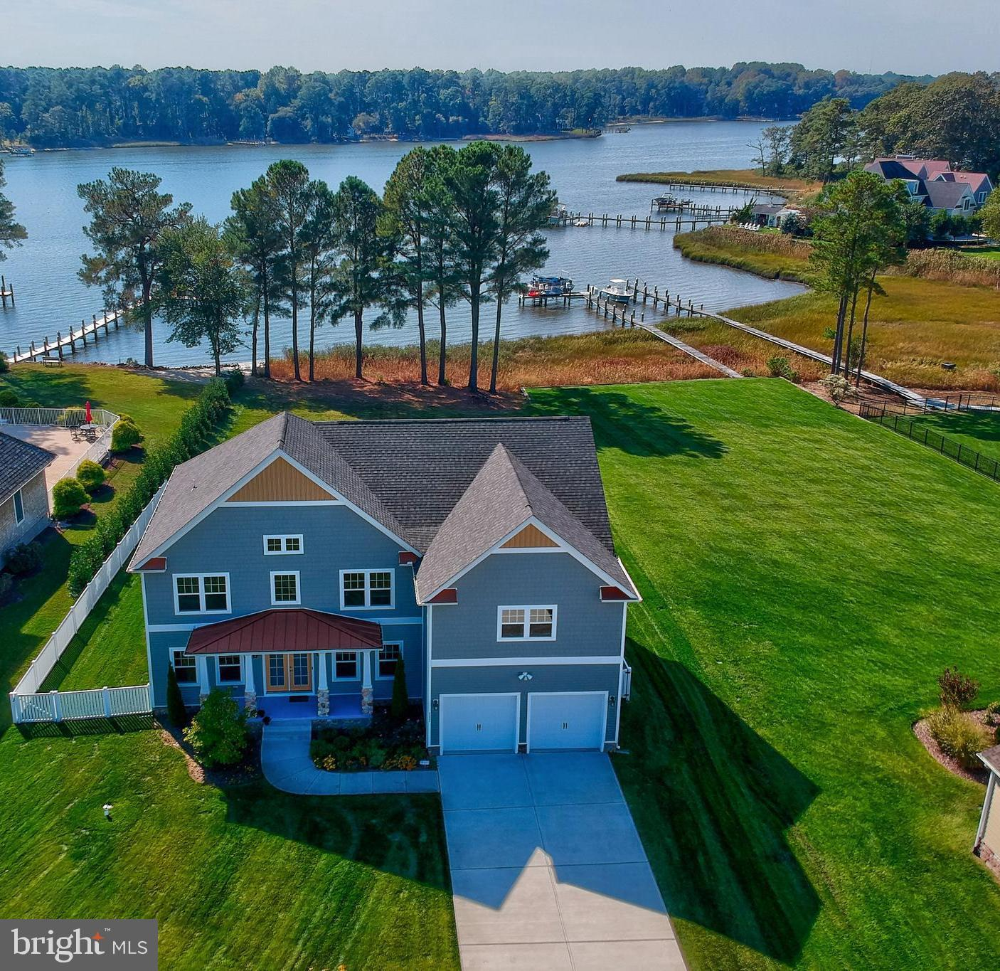 COASTAL. LUXURY. CUSTOM. This magnificent waterfront 5 bedroom, 3.5 bath home is ready for you to live, relax, and entertain. The fantastic open floor concept features beautiful flooring, large living areas, recessed lighting, a fireplace with gorgeous marble surround, a separate large dining area, and a wonderful enclosed back deck that looks out over the marvelous views of the bay. The gourmet kitchen features Bosch stainless steel appliances, granite countertops, beautiful ceramic backsplash, a wall oven with warming tray, induction cooktop, and contemporary cabinets. The large custom island has smart touch technology and the breakfast dining area leads to a comfortable bright and sunny family room with views of the water. You can reach the second level by elevator or stairs where you'll find a spacious master suite with large walk-in closets, a fabulous master bath with an extra large and fully tiled and stone shower, soaking tub, dual vanities, and vanity area. The other 4 bedrooms are bright, sunny, and airy, one of which was fully soundproofed and used as a music room. The large laundry features a wash sink, closet, washer and dryer. The expansive and partially fenced in backyard is a dream with unparalleled water views, beautiful landscaping, lots of space for entertaining, and the option to build a dock for your boat. The amenities at the Villages at Herring Creek include a clubhouse with meeting rooms, fully-equipped fitness room, tennis court, and an outdoor, 25-meter pool, all with surprisingly low HOA fees. This one-of-a-kind home with picturesque views is just a short drive to the beaches, shopping, restaurants, entertainment, and everything coastal Delaware has to offer. Make plans to visit today!