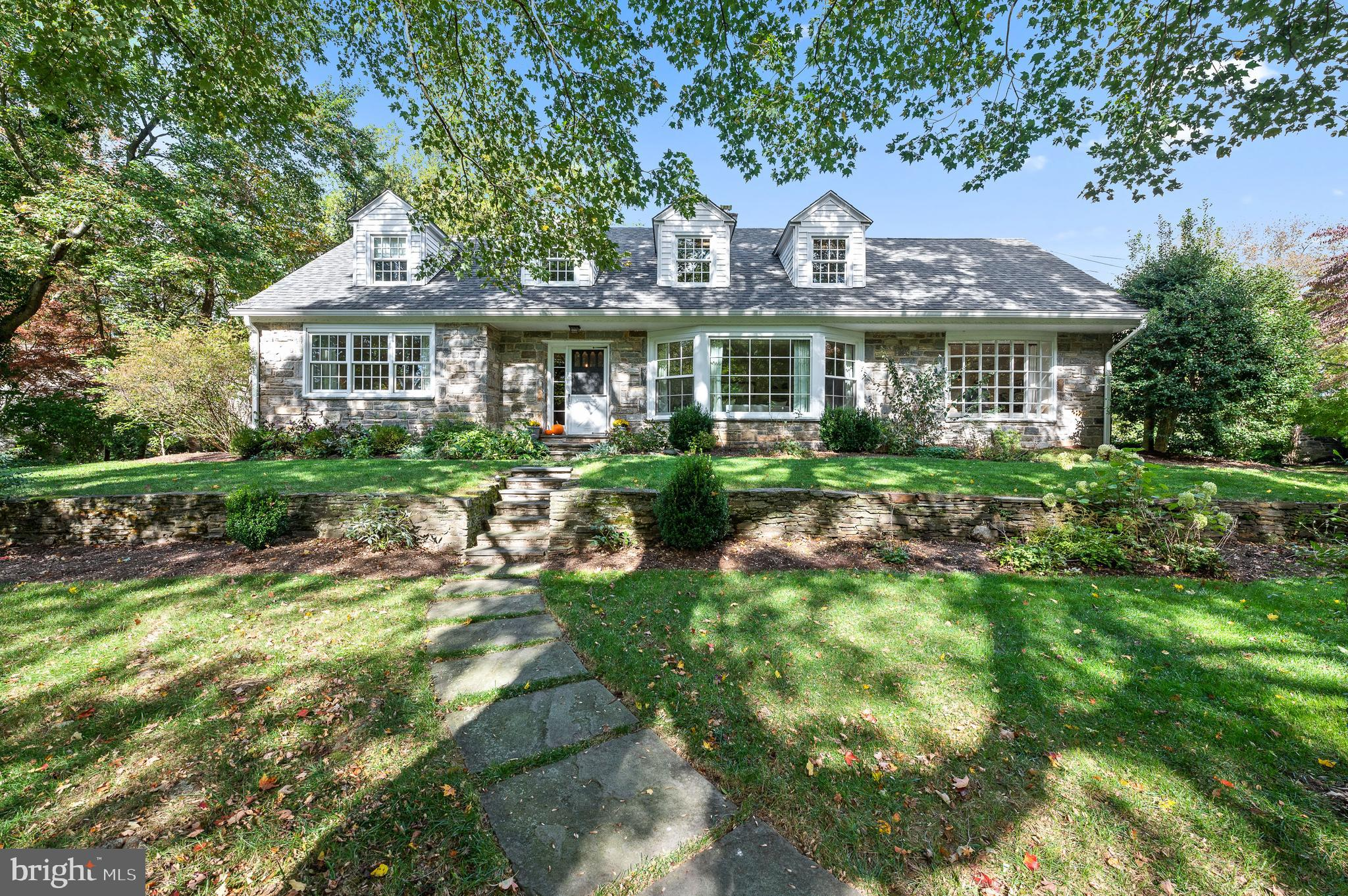Set in one of Wynnewood's most desired neighborhoods this charming sun lit stone cape cod will delight.  A flagstone walkway and stone garden wall lead you to the front door where you are greeted by hardwood floors, lots of windows allowing for sunny spaces and an appealing spacious layout with first floor primary suite.  The living room is wood paneled with a wood burning fireplace and a large wall of windows bringing the outside in! The dining room is light and bright and connects to the eat in kitchen which has great flow and is ready for your updates! The kitchen has an island and  a breakfast room sitting area. The laundry/mud room and pantry are adjacent to the kitchen. The family room is a cozy spot perfect for reading a book with Navy paneling, a wood burning fireplace, built-in bookshelves, and large windows overlooking the lush backyard and access to the back patio.  A charming powder room with white penny tile flooring is also conveniently located off of the family room.  A large Light Filled Main floor Primary suite is situated off the main foyer and features three closets and a full bath with double sinks and tub/shower. Upstairs there are hardwood floors throughout, a bedroom suite with full bath, and two additional spacious bedrooms sharing a hall bath, a cedar closet and a large storage area.  The lower level is a delightful space fully finished with a large recreation area and home theater, there is space for a gym, play room or home office and additional storage.  A detached 2 car garage and a lush backyard with raised bed garden complete with flagstone patio allow for expanded indoor/outdoor living.  With a new roof and gutters, newer HVAC, and Water heater this solid home is practically worry free!  Don't miss your opportunity to live in  Award Winning Lower Merion School District set in the most convenient location within walking distance to the train, bus, Wholefoods and shopping!